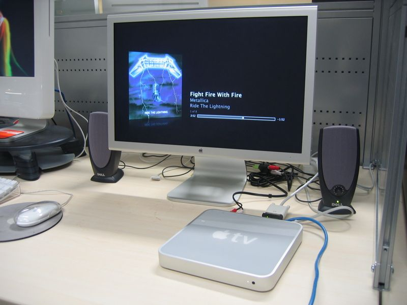 """A photo of an Apple TV connected to a 20"""" Apple Cinema Display and a pair of speakers, playing Metallica's """"Fight Fire With Fire""""."""