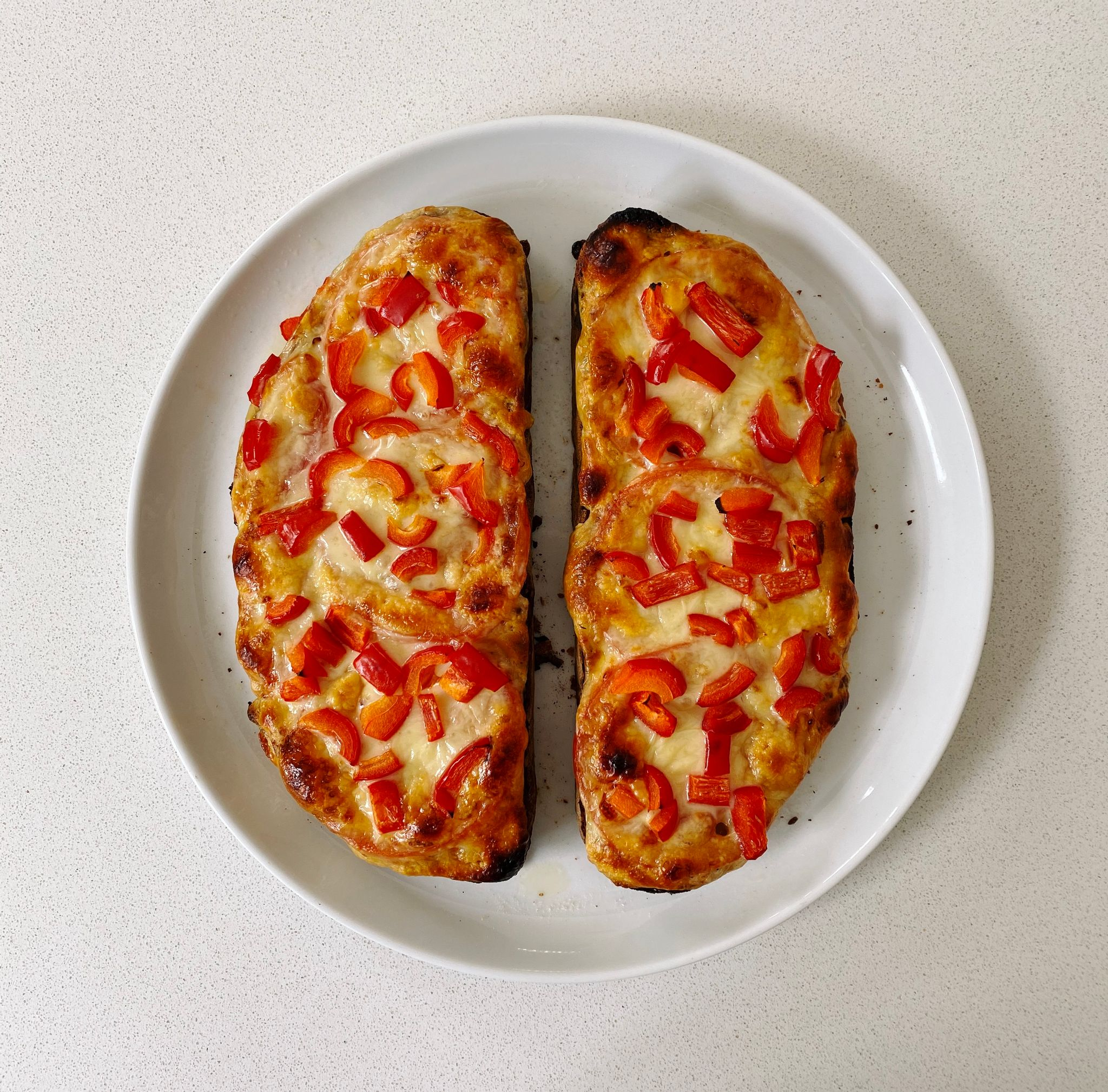 A photo of two cheese and tomato toasties sitting on a plate, with diced capsicum on top.