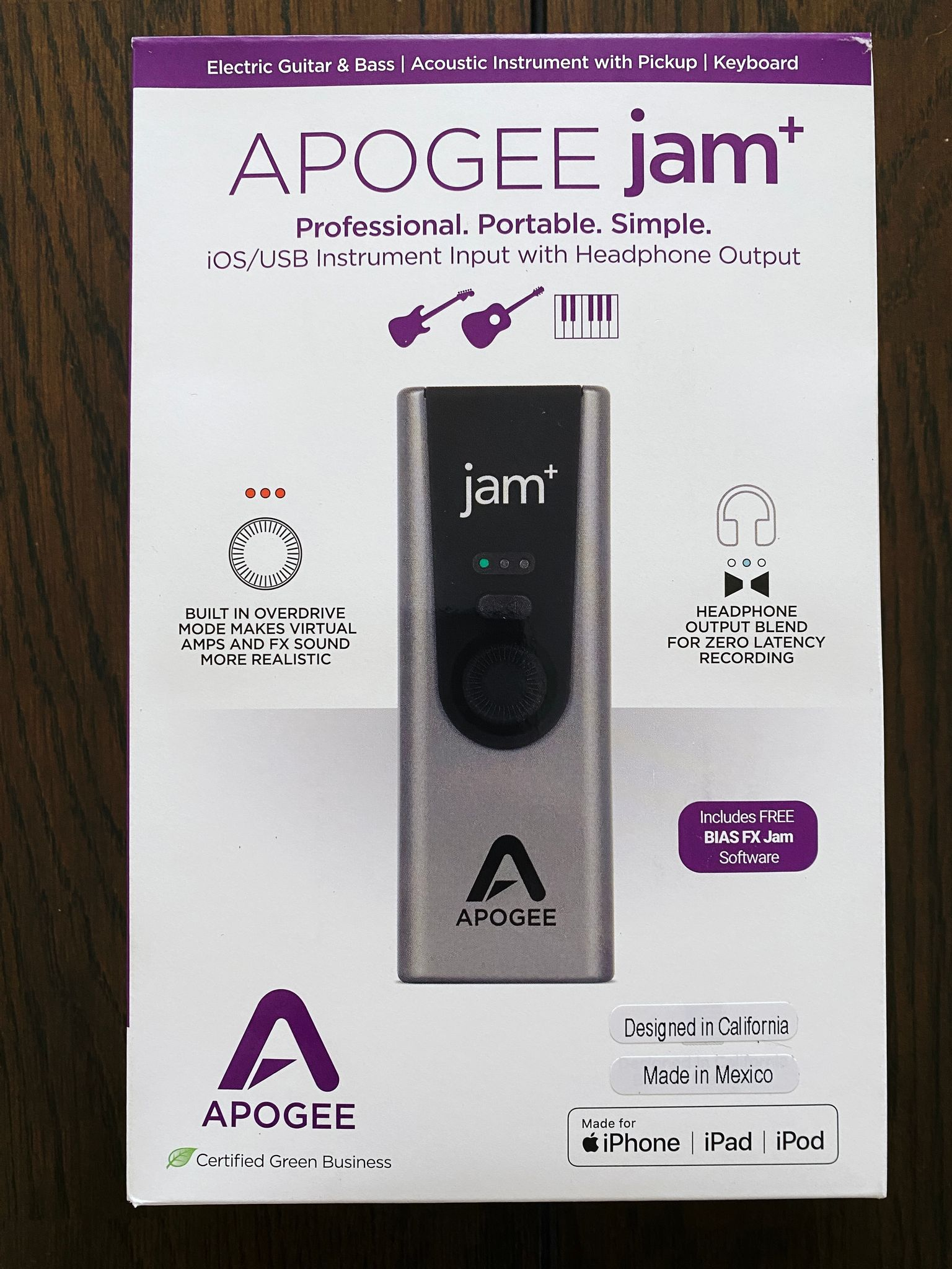 """A photo of the box of Apogee's """"Jam"""" guitar input, an unassuming silver rectangle with a dial on the front as well as a button and some lights."""