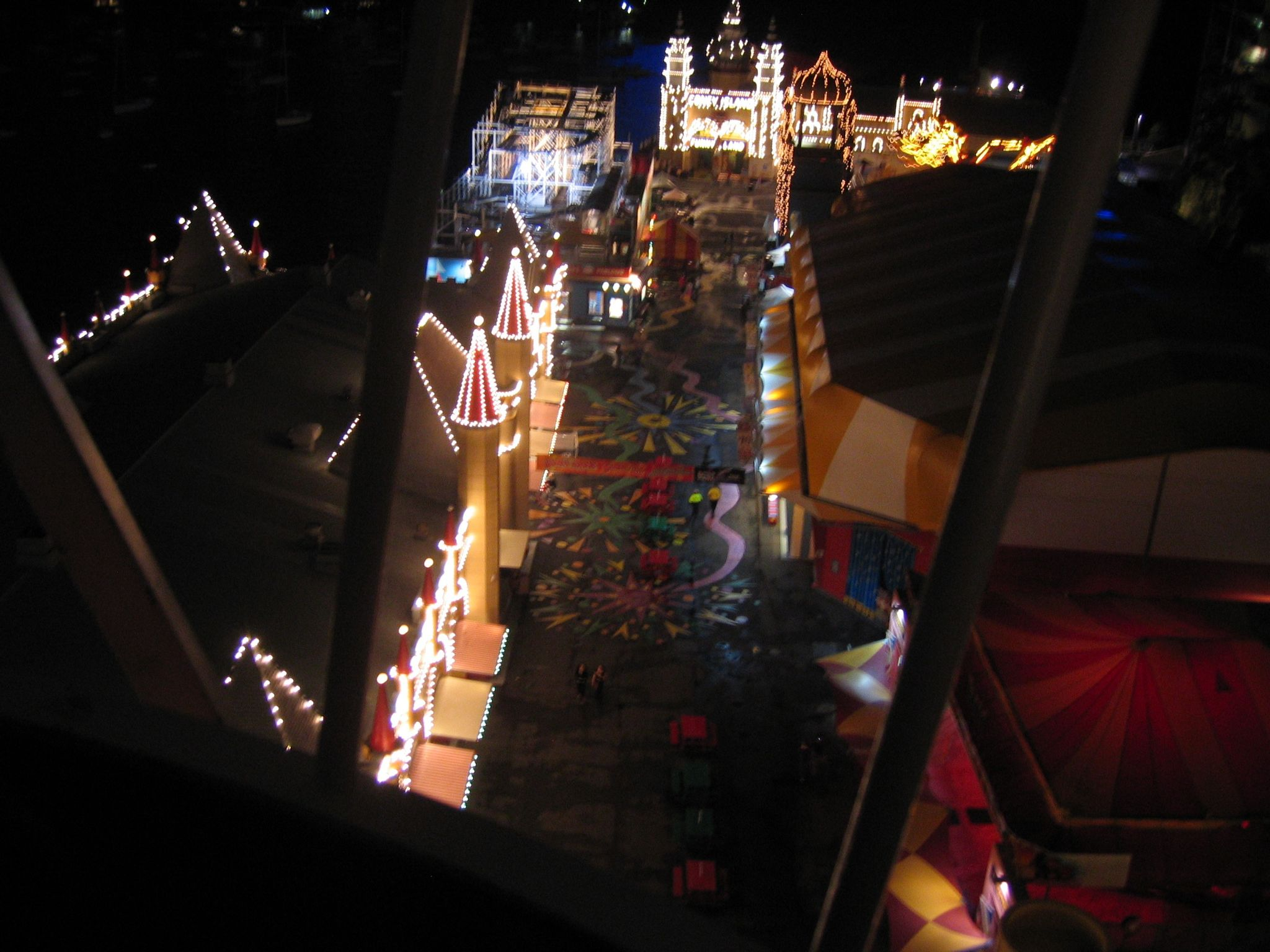 A photo looking down the quite large distance to the ground from the top of a ferris wheel. You can see a lot of Luna Park and there's lots of buildings adorned with lights.