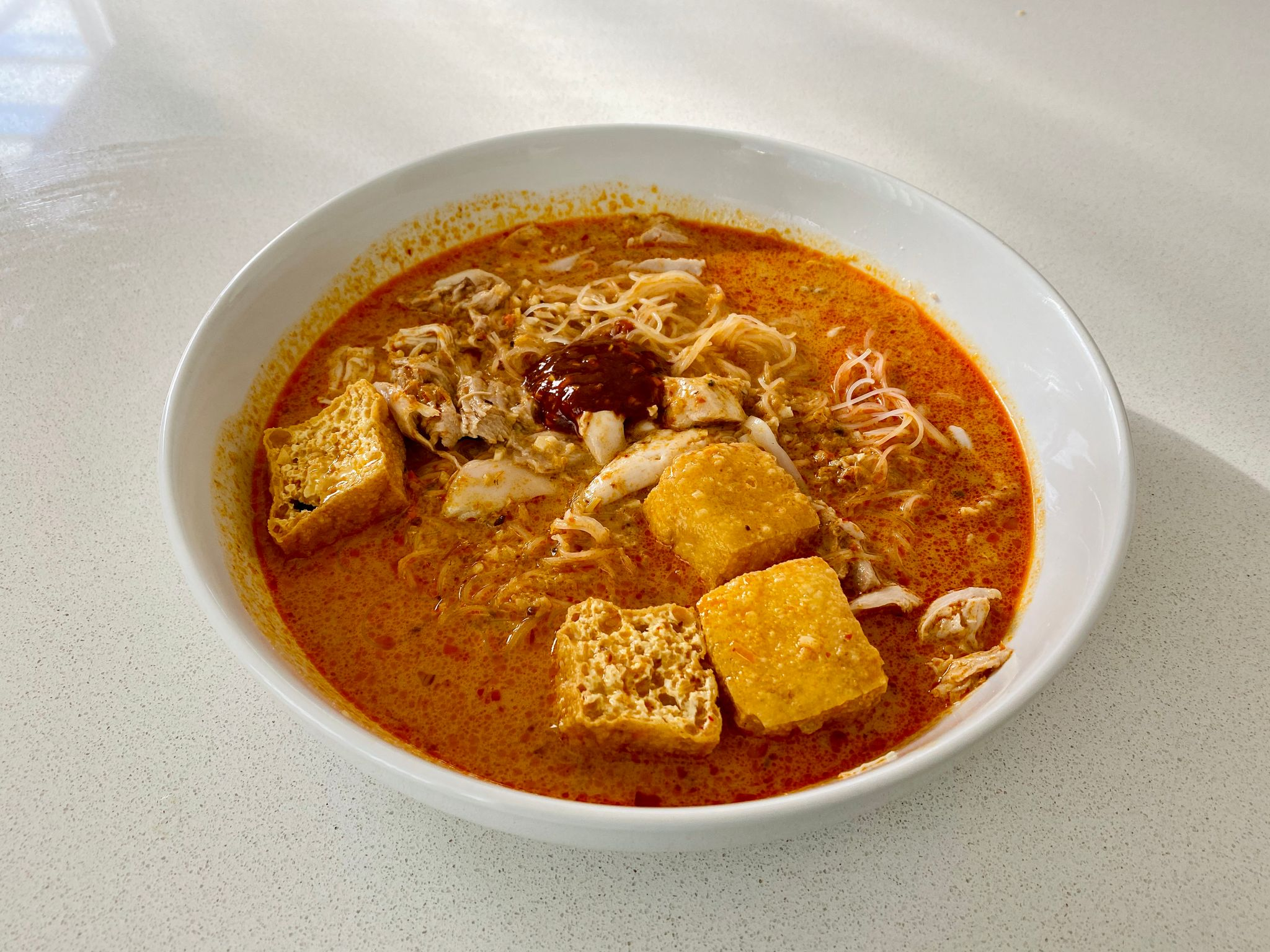 A photo of a bowl of laksa with fried tofu puffs and a dollop of home-made chilli sauce on top.