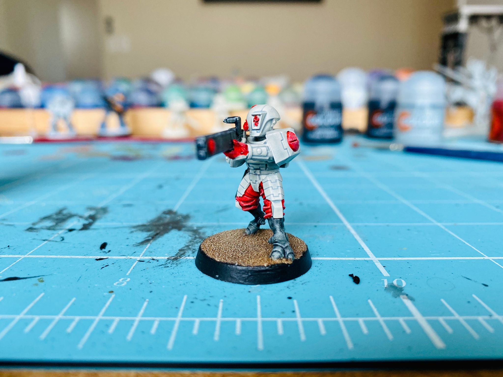 A photo of a Tau Fire Warrior from the Warhammer 40,000 Kill Team box. It has white armour plates and helmet, black feet, and red cloth clothing underneath, and is looking down the barrel of a long black alien-looking laser rifle.