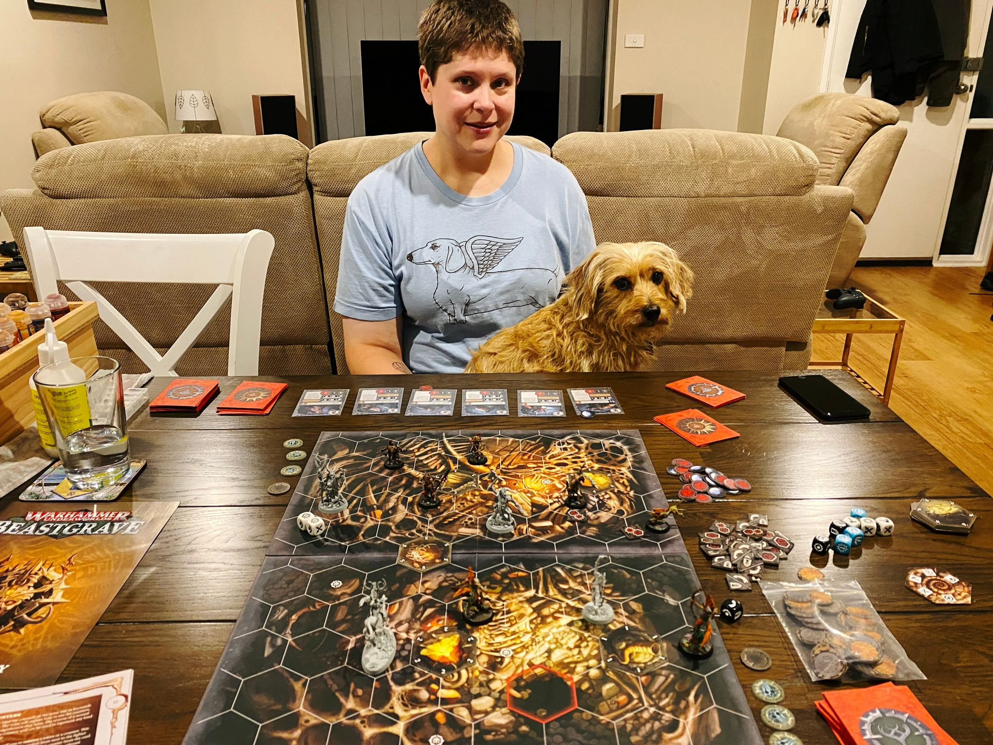 A photo of a table with a board and miniatures on it, with a white woman with short hair sitting on the other side of the table and smiling. She has a small scruffy blonde dog sitting in her lap who is also looking at the camera.