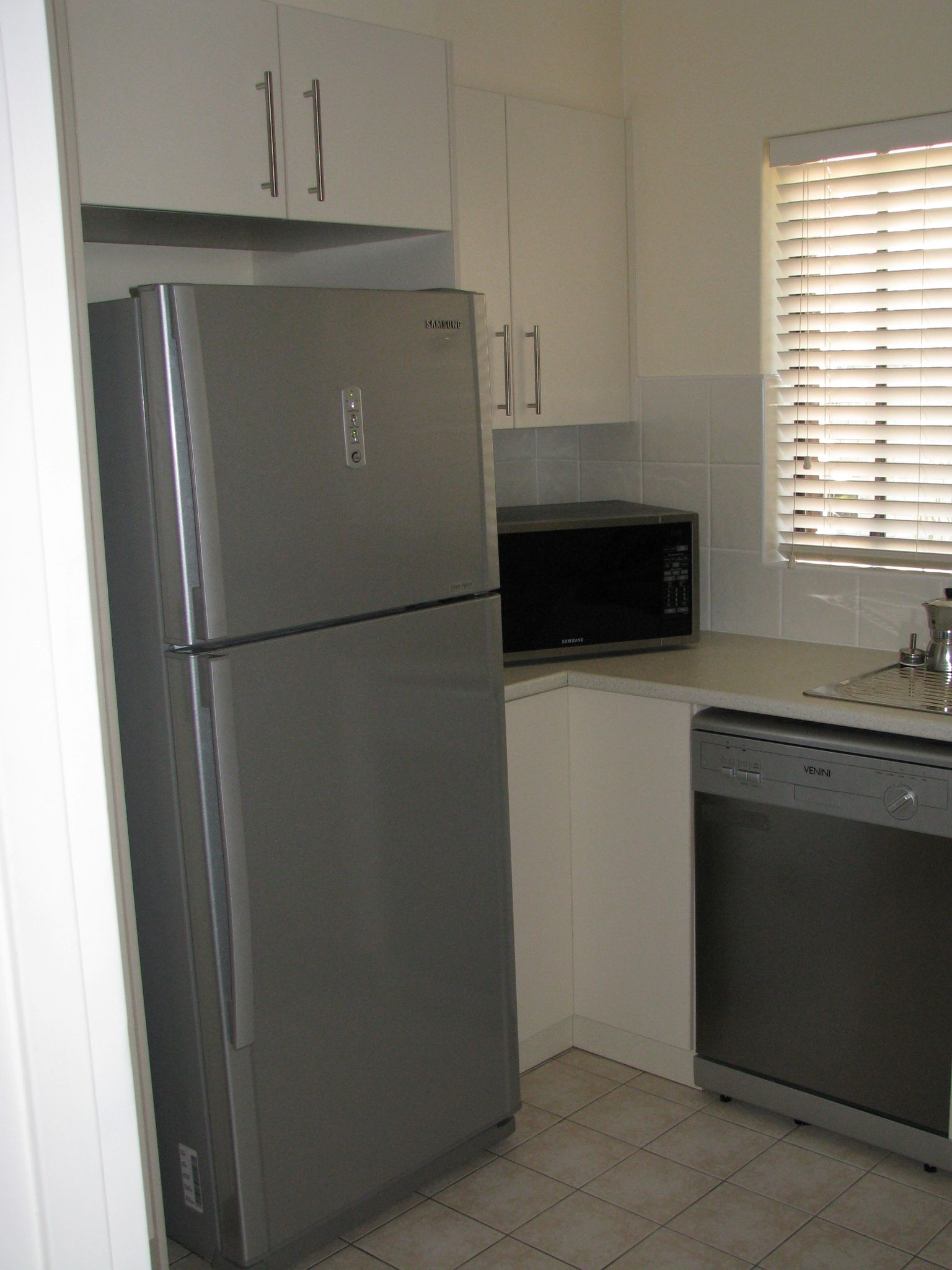 A photo of the corner of the kitchen, with the dishwasher on the right, a microwave jammed into the corner, and a metal-fronted fridge to the left of the microwave.