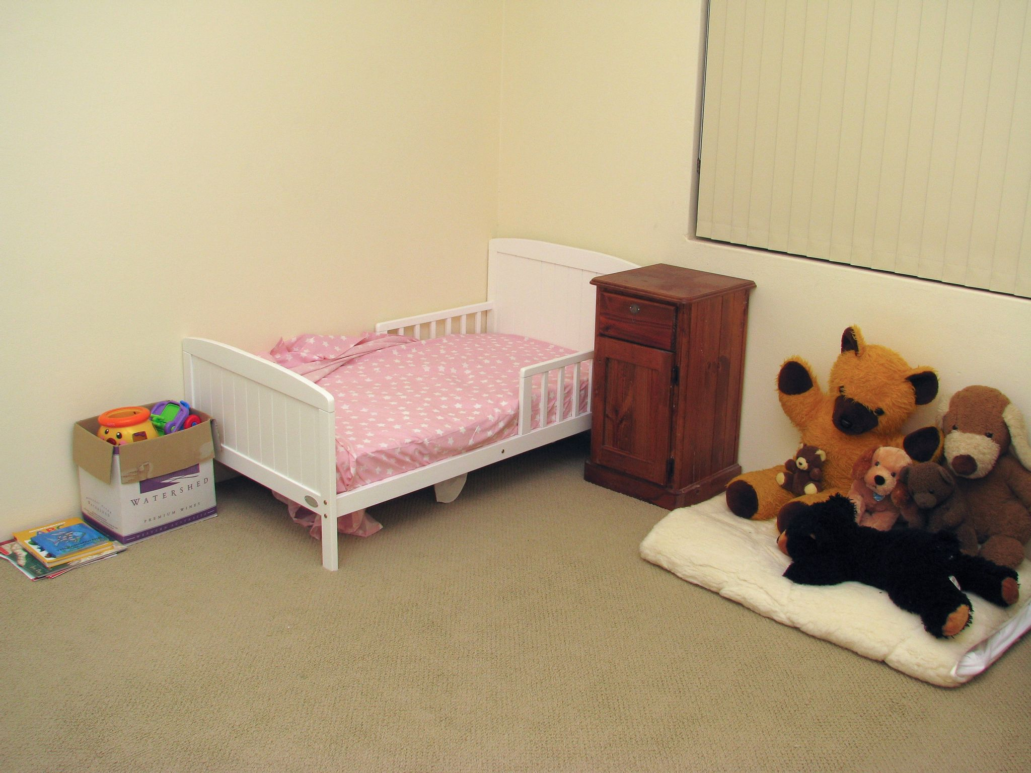 A photo of a small white wooden toddler bed in the corner of a room, with pink sheets on it. There's a brown wooden bedside table next to it that's significantly taller than the top of the bed, various soft toys to the right of the bedside table, and some plastic toys in a box at the end of the bed.