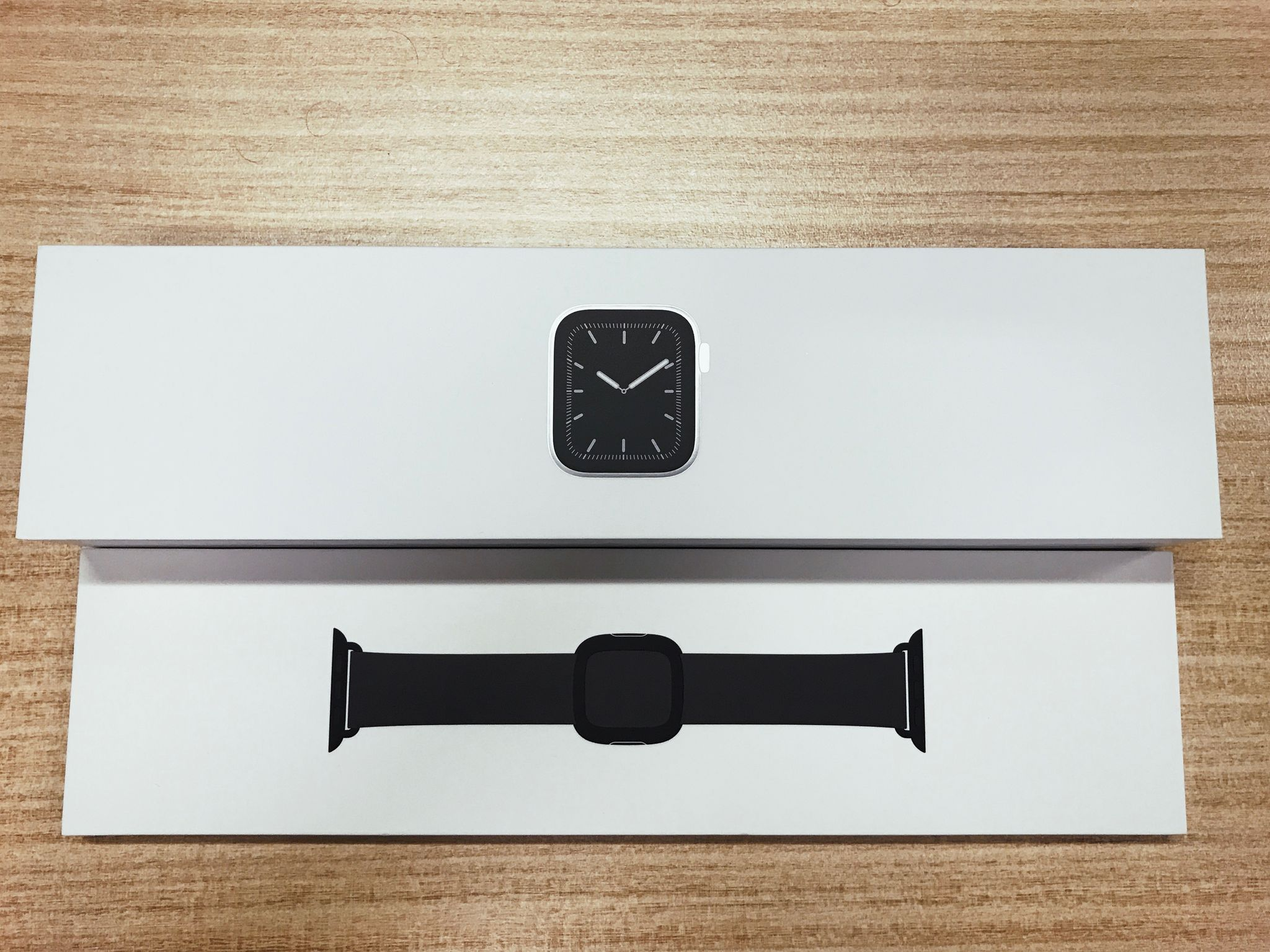 A photo of the boxes of an Apple Watch Series 5 and a band.