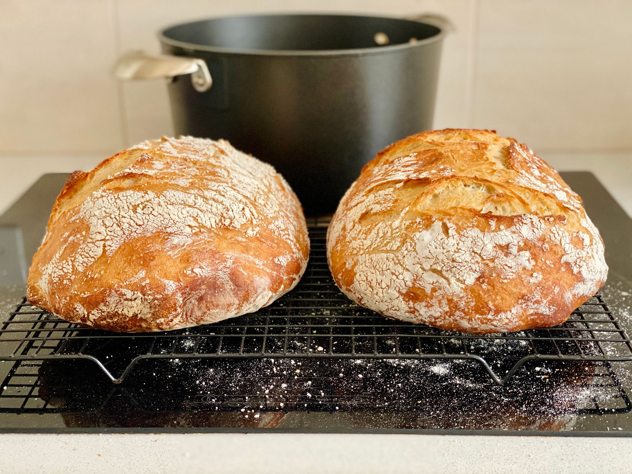 A photo of two golden round loaves of white bread sitting on a cooling rack.
