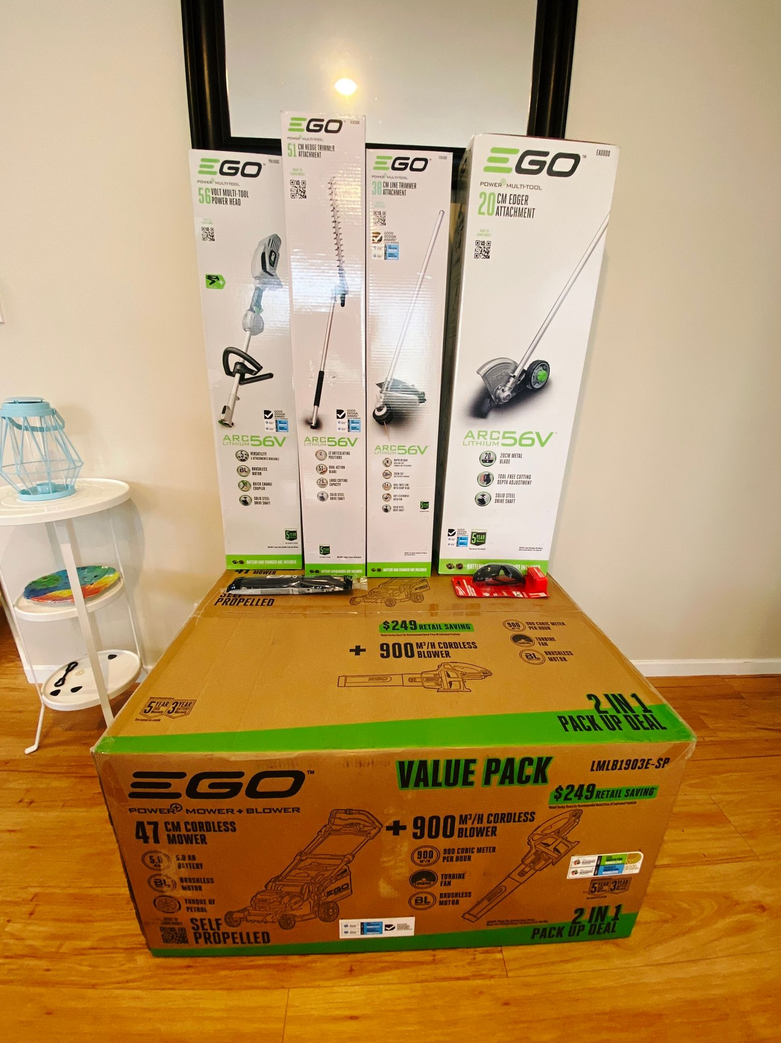 A photo of a BUNCH of big boxes containing all battery-powered equipment: lawn mower, blower, plus an edger, hedge trimmer, and line trimmer attachment and the head they attach onto. Also a shoulder strap and a pair of polarised protective glasses.
