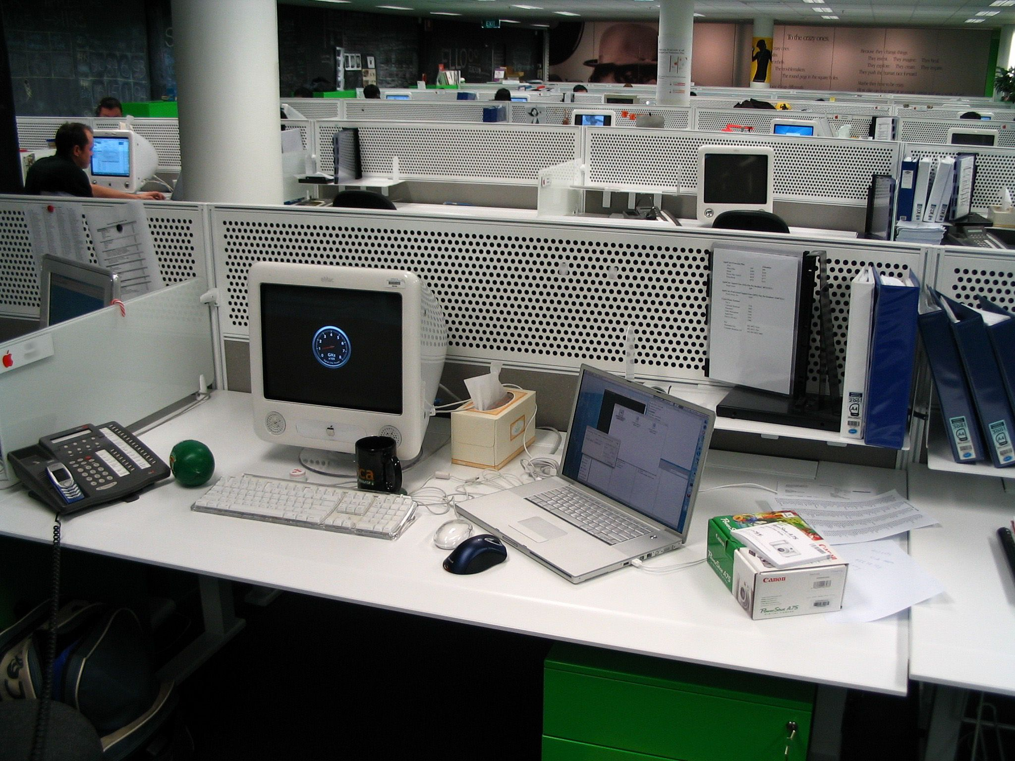 "A photo of my desk at work in a call centre. The same 17"" PowerBook G4 and PowerShot box are visible, but next to it is my work machine, an eMac, with a black Ars Technica mug in front of it. To the left of the eMac is a grey call centre phone, with my mobile phone sitting on top of it."