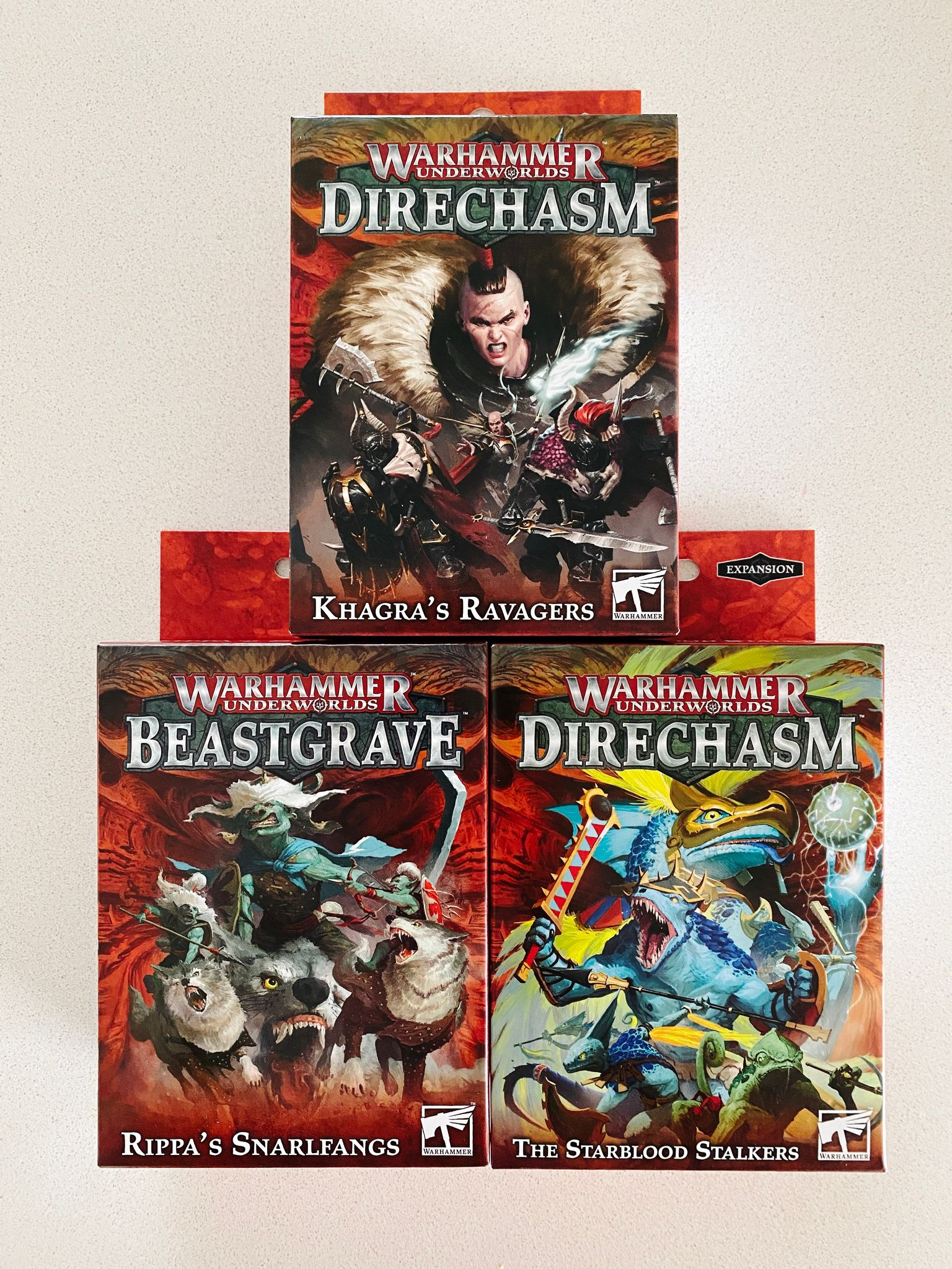 A photo of the boxes of three warbands from Warhammer Underworlds: Khagra's Ravagers (Chaos warriors), Rippa's Snarlfangs (goblins on wolfback), and the Starblood Stalkers (Aztec-feeling lizards).
