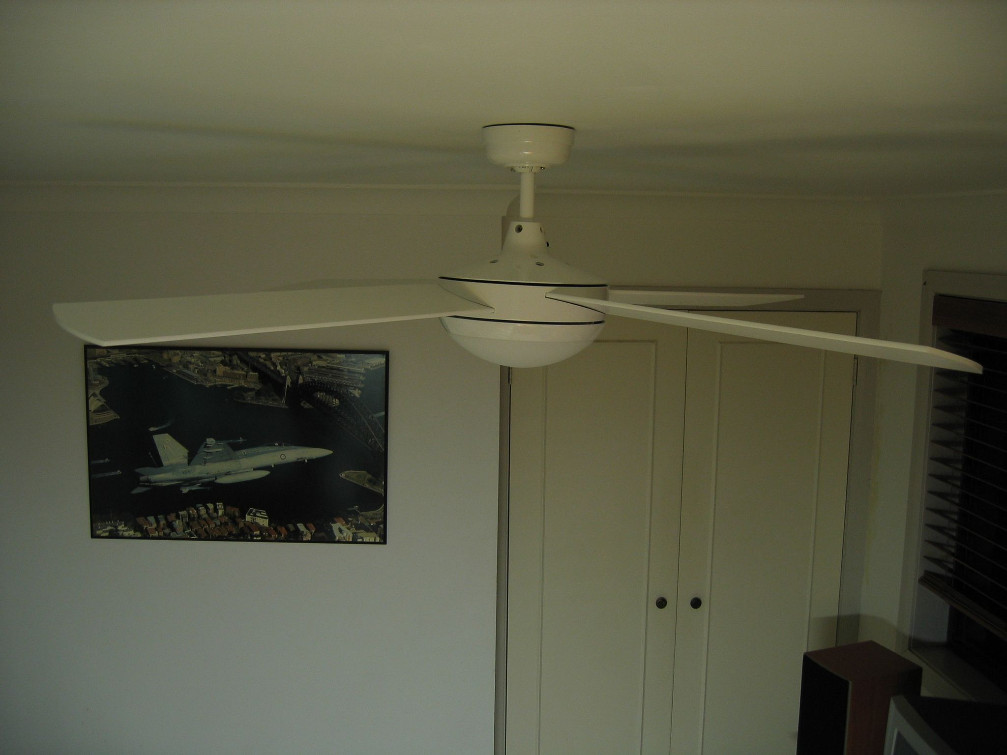 A photo taken from high up towards the ceiling looking directly across towards a ceiling fan. Past the fan is a pair of cupboard doors, and a poster on the wall of an F/A-18 Hornet jet fighter flying over the Sydney Harbour Bridge.