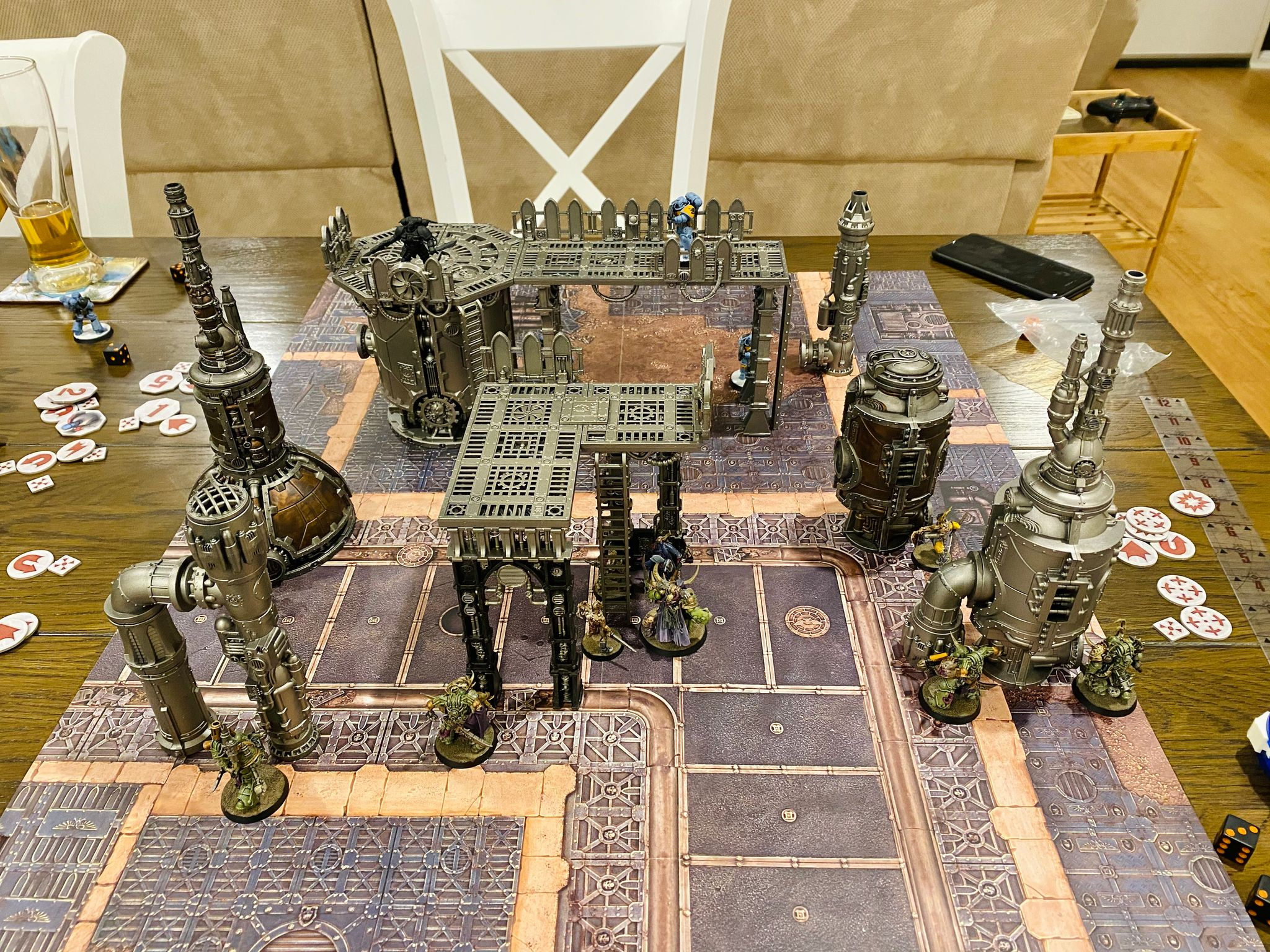 A photo of a table with the current Kill Team box set terrain set up on it (very industrial, lots of tall metal-looking structures), with Death Guard facing off against Space Wolves.