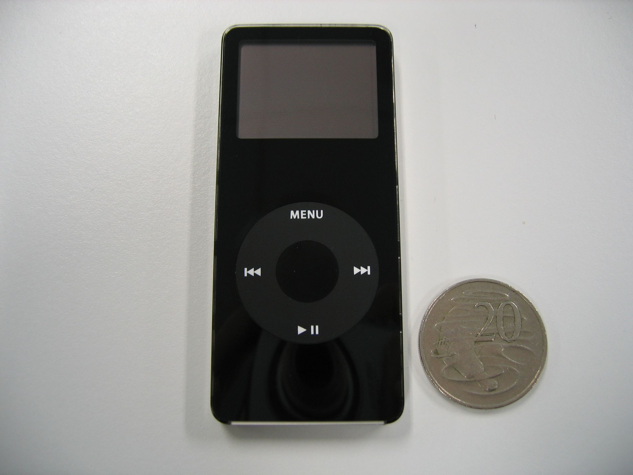 A photo of a black iPod nano sitting next to an Australian 20-cent coin. The 20c coin is about three-quarters as wide as the iPod is.
