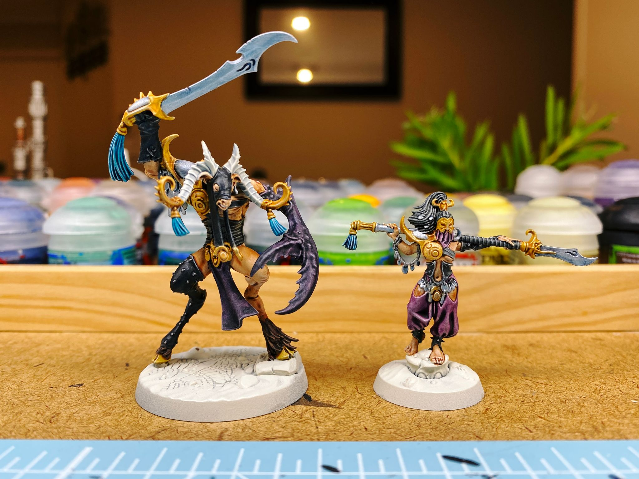 A photo of painted two miniatures. One is a tall but hunched over goatman wearing leather and wielding a sword over its head. The other is a woman with a corset, Middle-Eastern type puffy pants and a gold mask with a purple face covering, and holding a glaive over her shoulders.