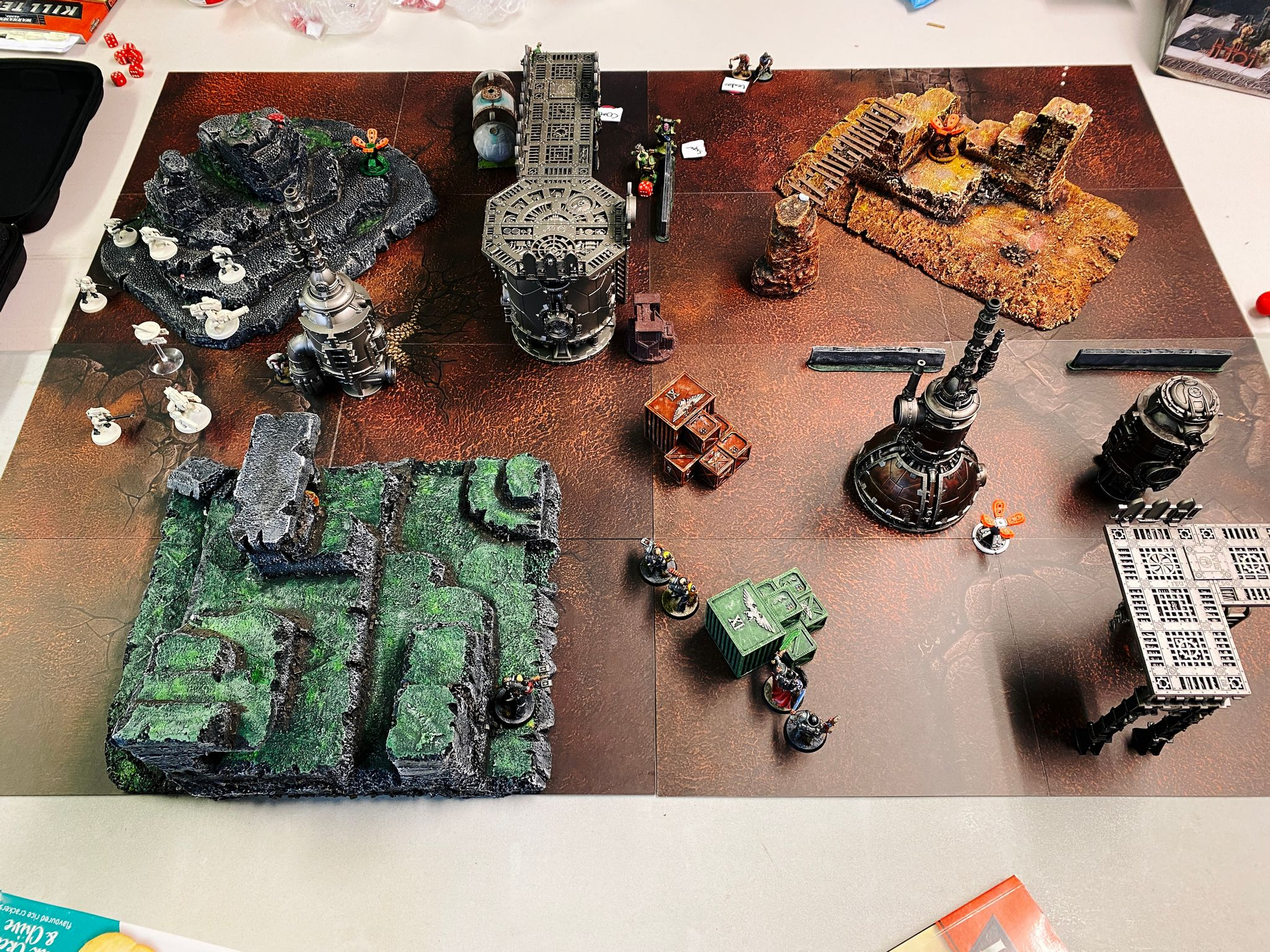 A photo of a Warhammer 40K Kill Team board with terrain in it. There's a bunch of industrial-looking bits at the right side, and some granite stony-looking craggy tiered cliffs on the left.
