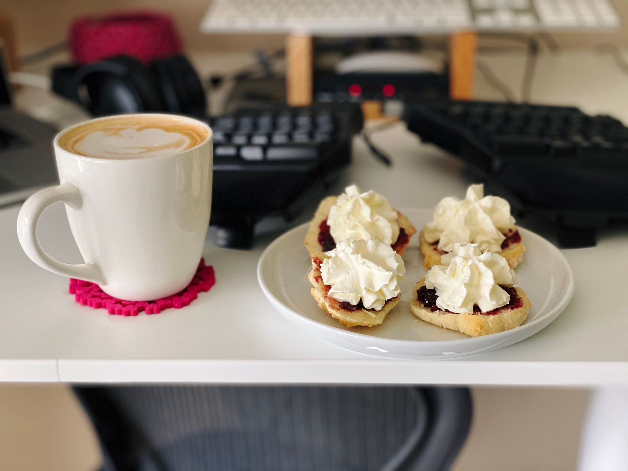 A photo of two scones sliced in half with jam and whipped cream on top, sitting on a plate next to a mug of coffee.