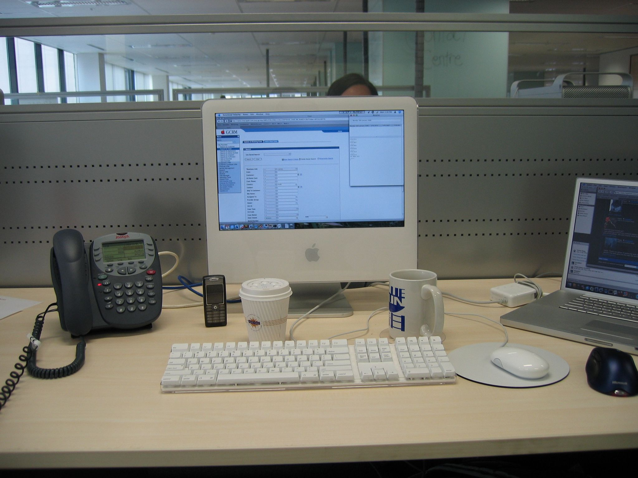 "A photo of my work desk. The desk itself is a light-coloured wood veneer surface, with a grey metal panel behind it. An iMac G5 is sitting the middle, with a 17"" PowerBook G4 to the right of it, and a grey call centre phone to the left."