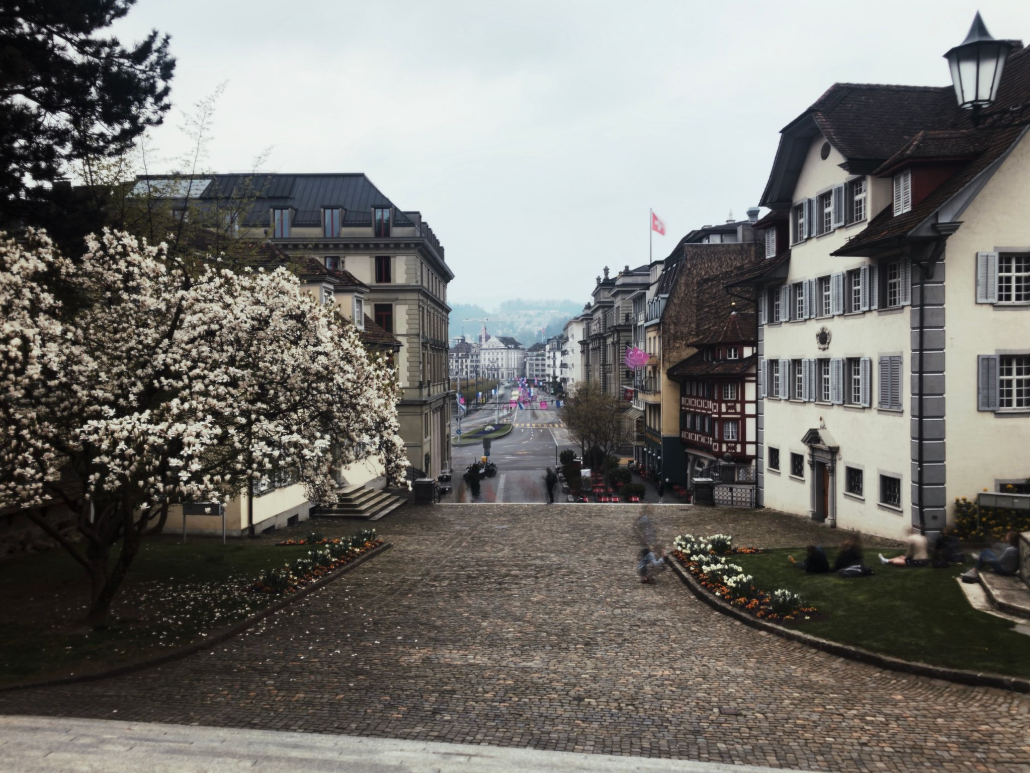 A view down a main street in Lucerne, with tram tracks running down it, old buildings on the right side, and trees beside a river on the left.
