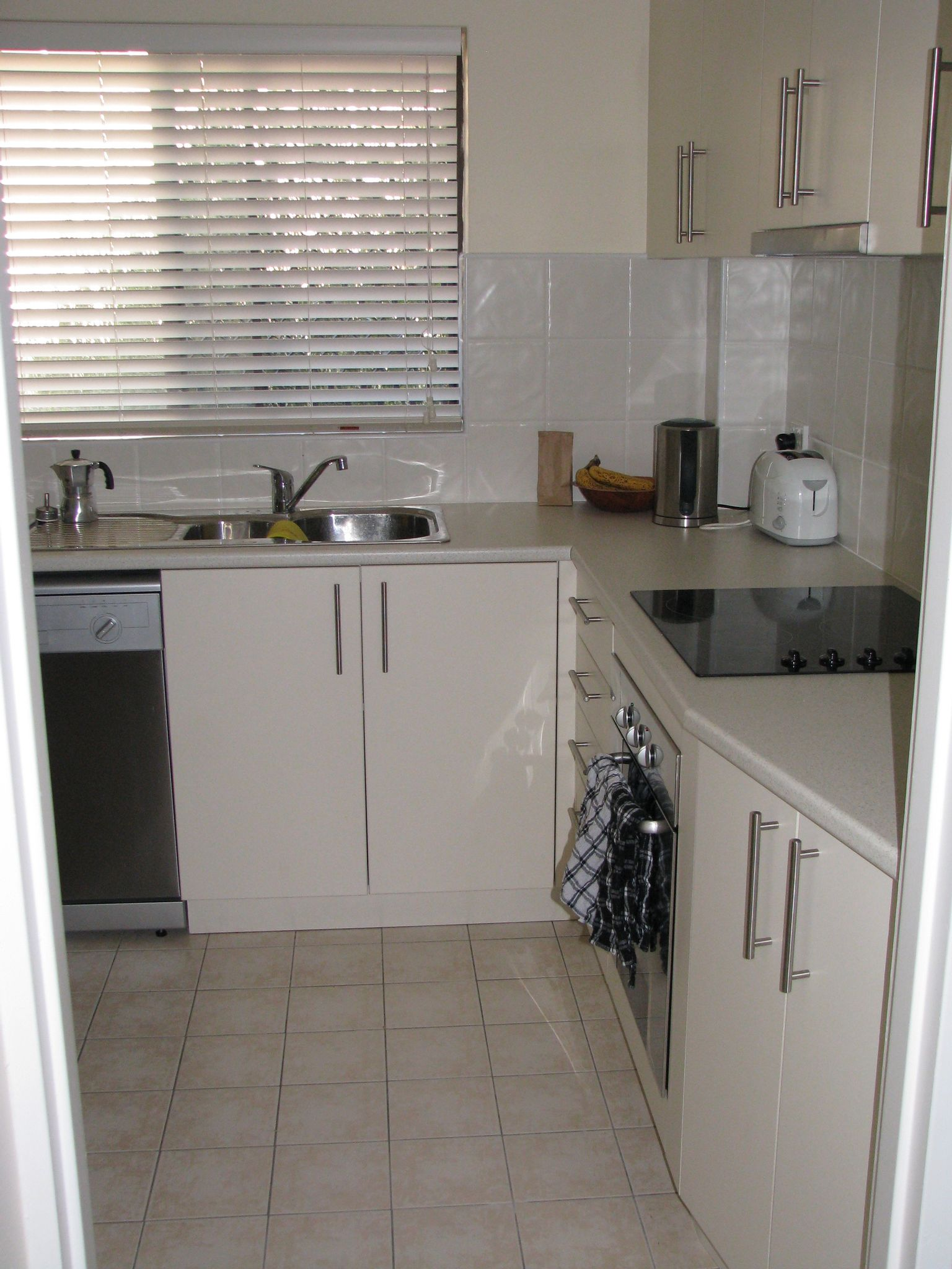 A photo looking into the kitchen from outside the doorway. The cupboards are cream coloured, there's a ceramic cooktop on the bench at the right, the sink is facing the doorway, and there's a dishwasher just visible to the left of the sink.