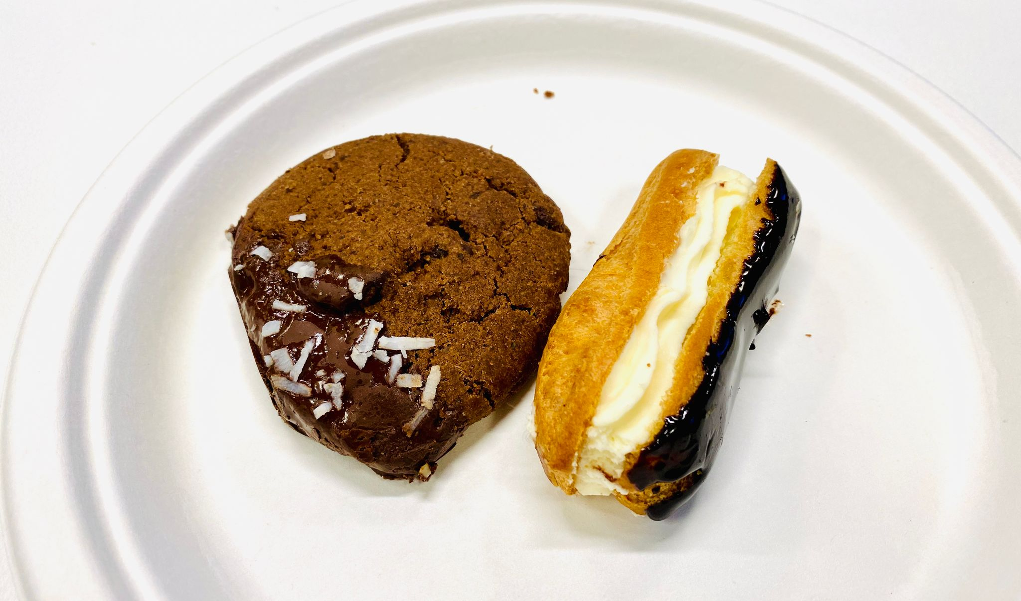 A photo of a vegan chocolate cookie and a decidedly not-vegan chocolate eclair on a plate.