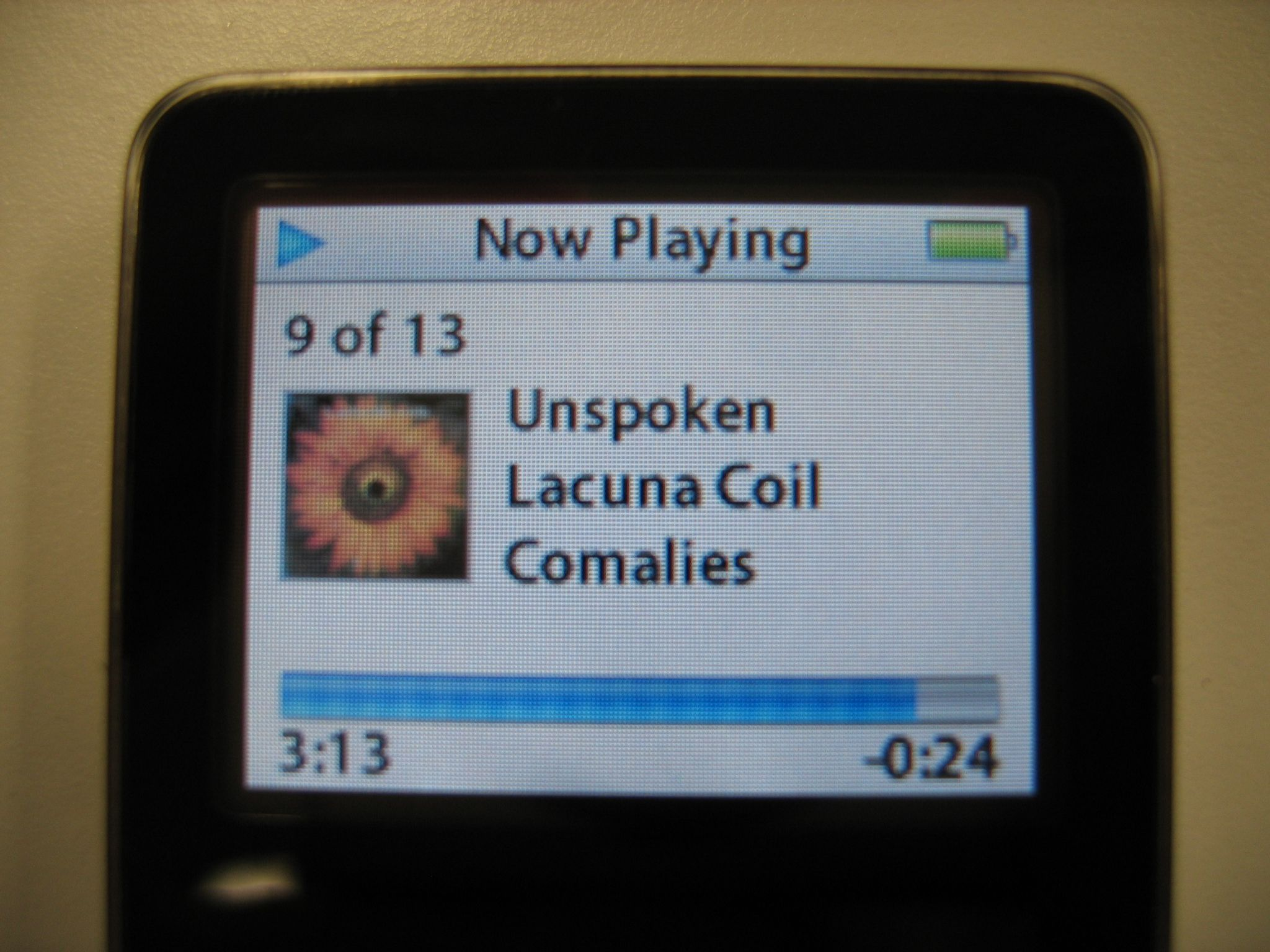 A photo of the screen of an iPod nano showing a song playing.