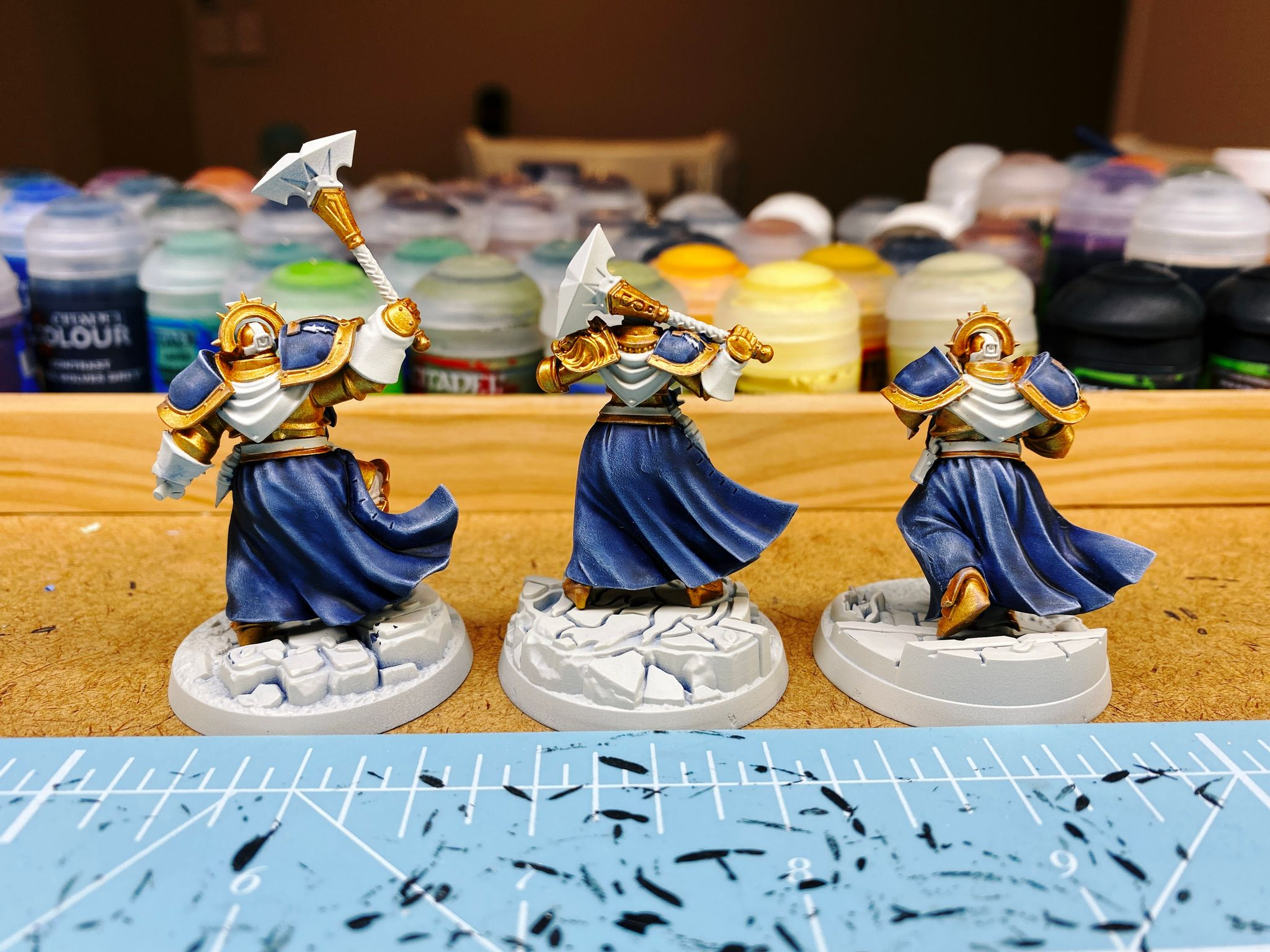 A photo of the back of the three partially-painted miniatures from the Ironsoul's Condemnors warband from Warhammer Underworlds. They're heavily armoured with gold armour, and have long flowing robes in dark navy blue. The raised edges of the robes are highlighted in a wonderfully smooth fashion up to a light blue, almost like they've been airbrushed.
