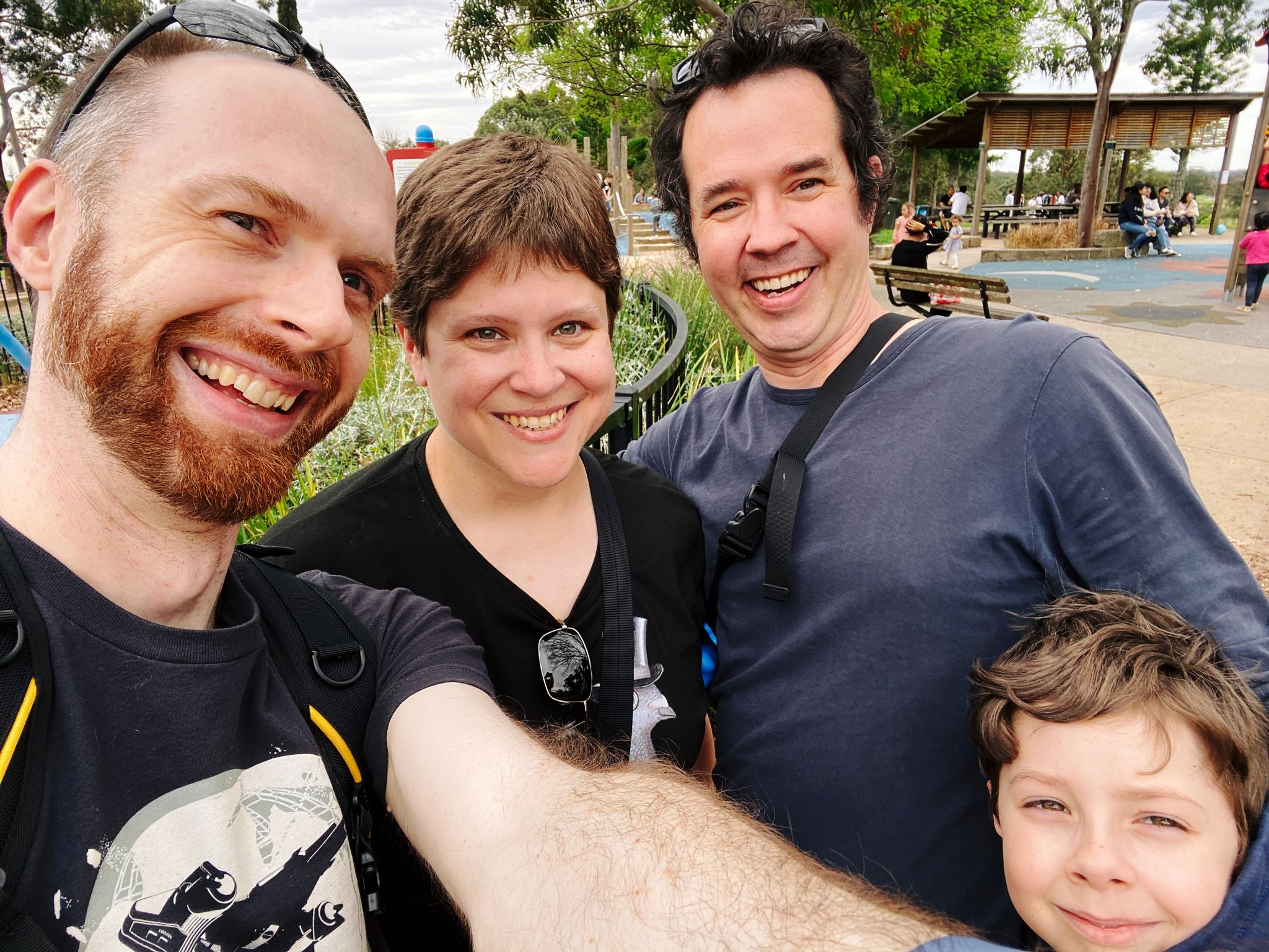 A selfie of four white people, me, a man with a red beard and short hair, Kristina, a woman with short brown hair, Andrew, a tall man with poofy-out dark hair, and Andrew's son Alex, a boy of about 7 with mousey brown hair who's only just in frame at the bottom right because he's so much shorter than the rest of us.
