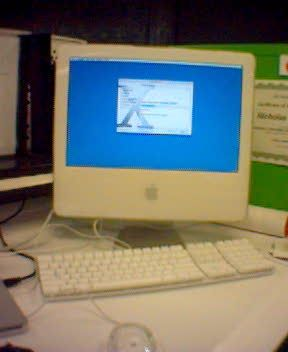 A photo of an iMac G5 sitting on a desk with the Mac OS X installer on screen.