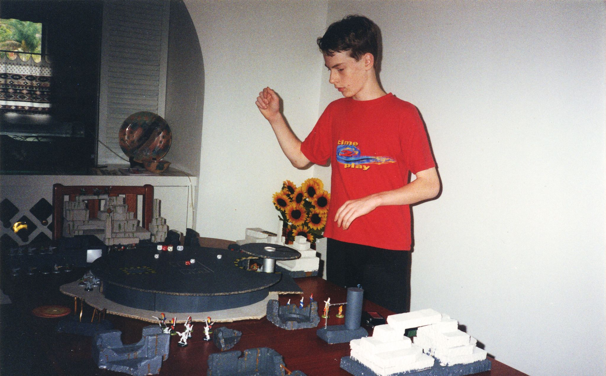A photo of me, a just-thirteen year-old white boy with short brown hair and a red (!) t-shirt on, looking extremely serious and with my hand in the position that indicates I've probably just rolled some dice.