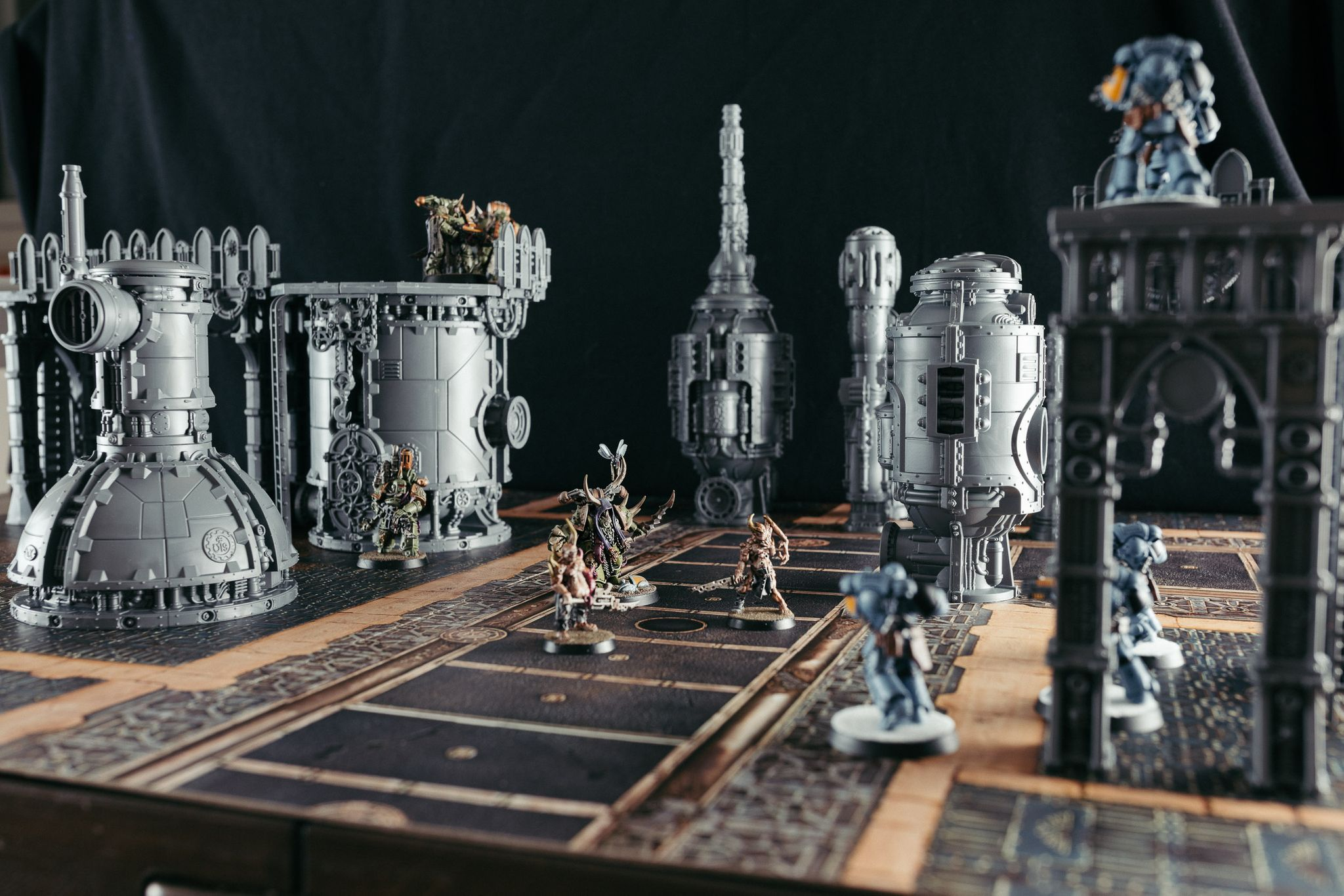 A photo of some Death Guard and Space Wolves miniatures on the new Kill Team starter box terrain. The terrain itself is unpainted grey plastic but is towering over the miniatures and has a very steampunk aesthetic to it.
