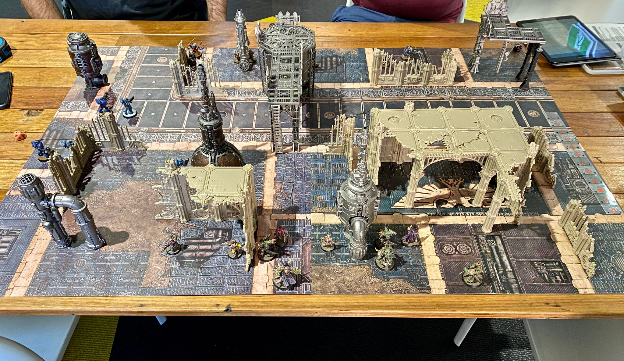 A photo of a game of Warhammer 40K: Kill Team, with industrial-looking terrain mixed in with gothic cathedral ruins spread across two of the standard size game boards.