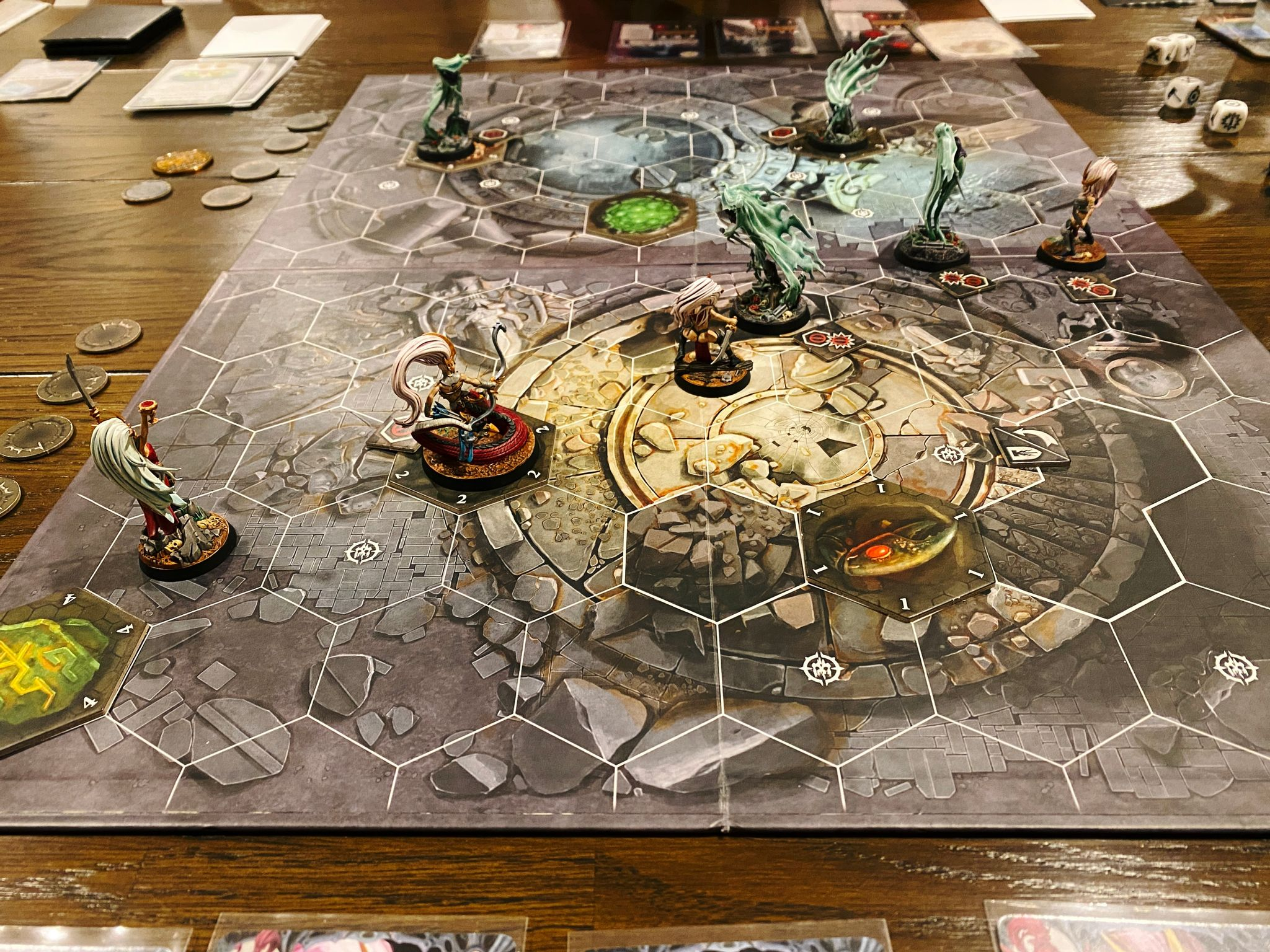 A photo of a game of Warhammer Underworlds. The two warbands being played are Lady Harrow's Mournflight, which are ghostly flowing spirit-looking miniatures, and Morgwaeth's Blade-coven, which are lithe aelves wearing not too much armour.