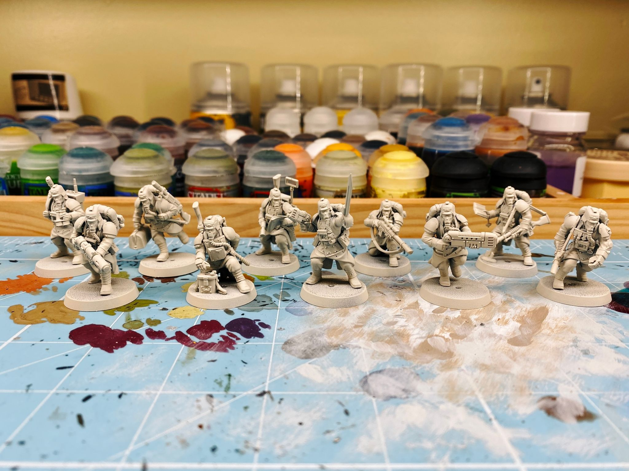 A photo of the ten Death Korps of Kreig miniatures from the Warhammer 40,000 Kill Team: Octarius box. They're all human but with big greatcloaks on and wearing gas masks. There's very much a World War 1 vibe going on.