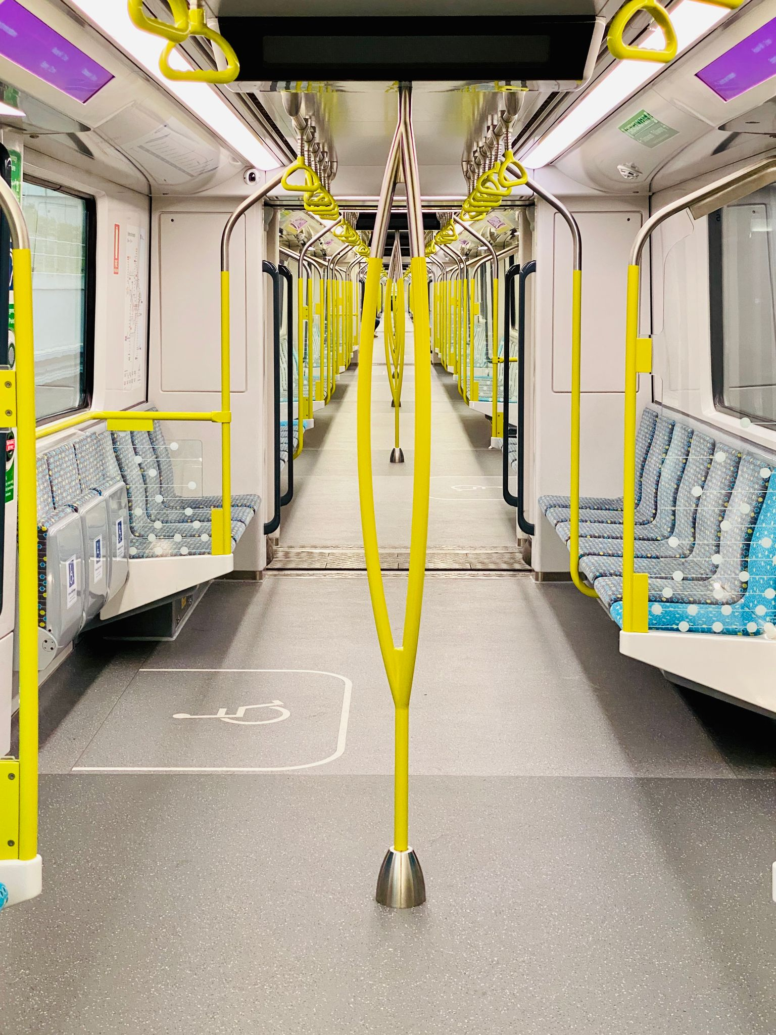 A photo looking down the entire inside length of a Sydney Metro single deck train. There's almost nobody on it.