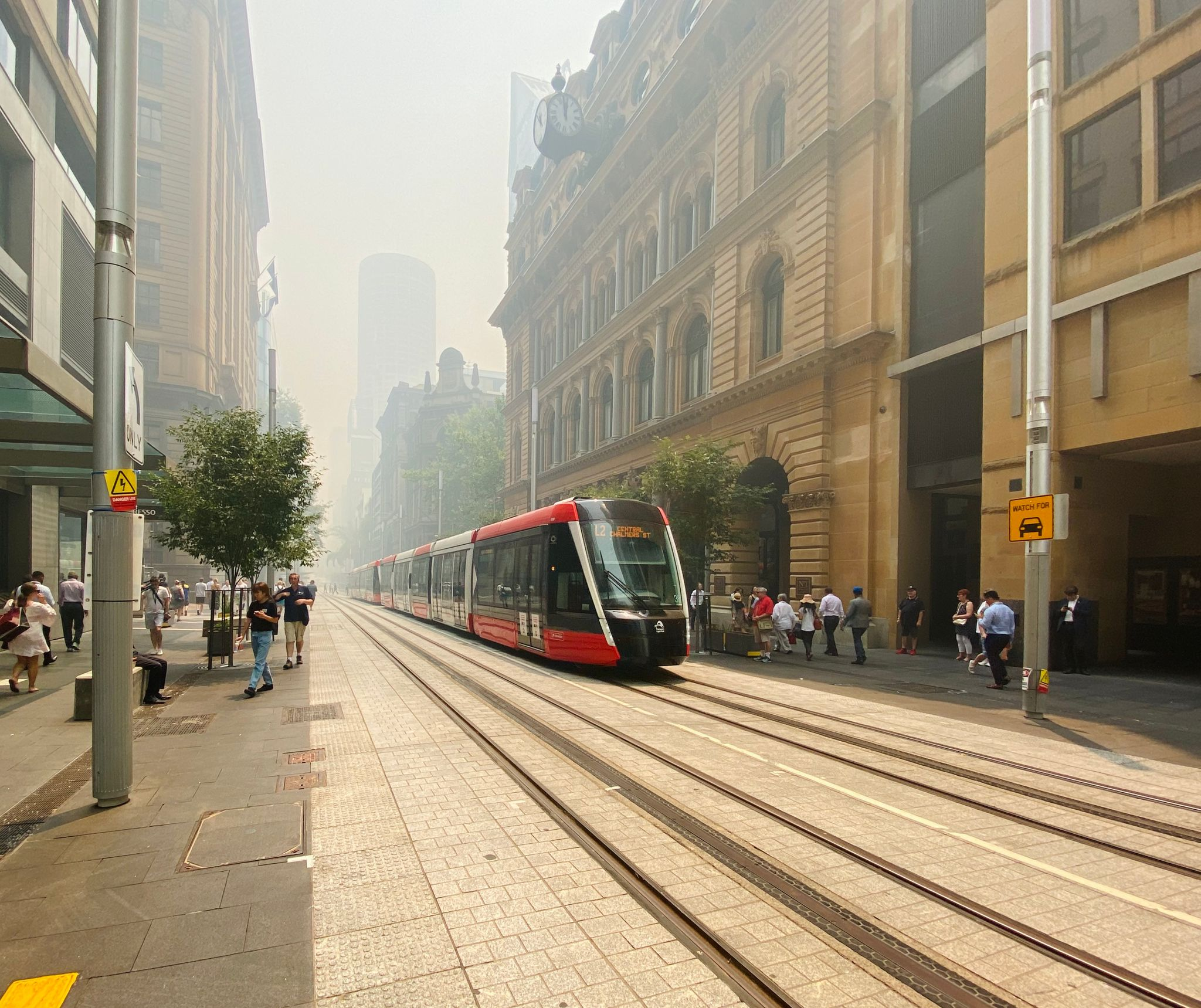 A photo looking down George St in Sydney's CBD. A tram is moving down the street and the entire scene is hazy and the distance is invisible thanks to the amount of bushfire smoke in the air.