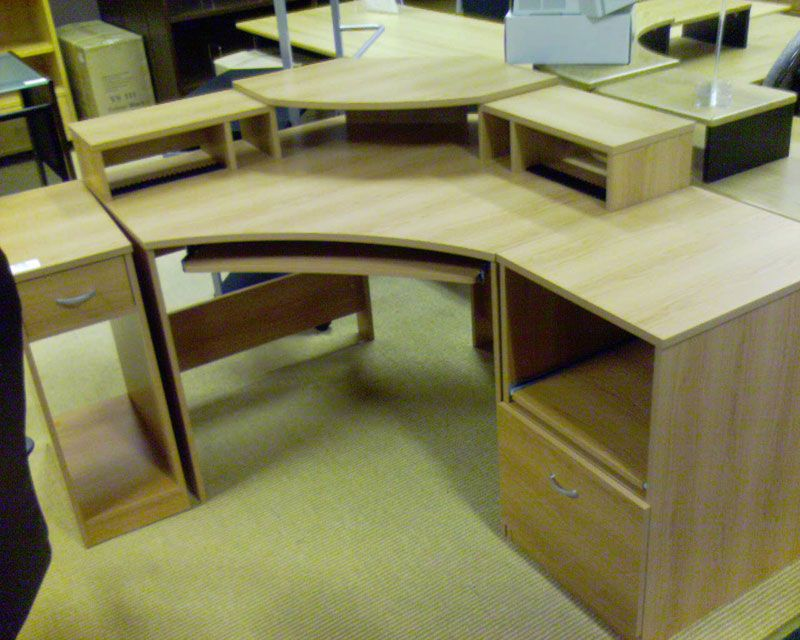 A photo of a wood-veneer corner desk in a shop. There's three raised sections in the middle corner piece where monitors can go.