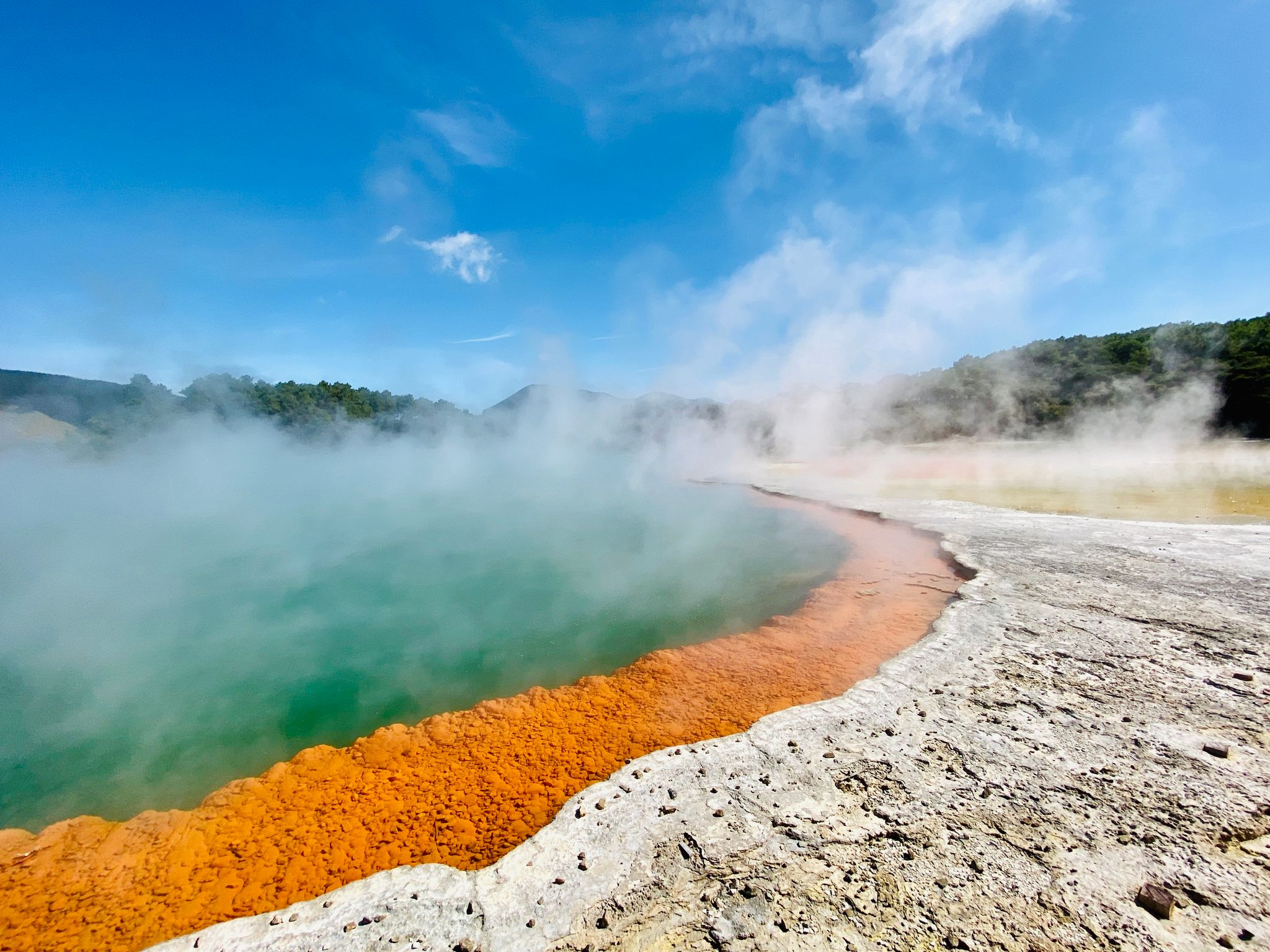 A photo of geothermal springs, the water is incredibly blue, there's a band of orange rock just at the edge of the water, and steam is billowing up from the surface.