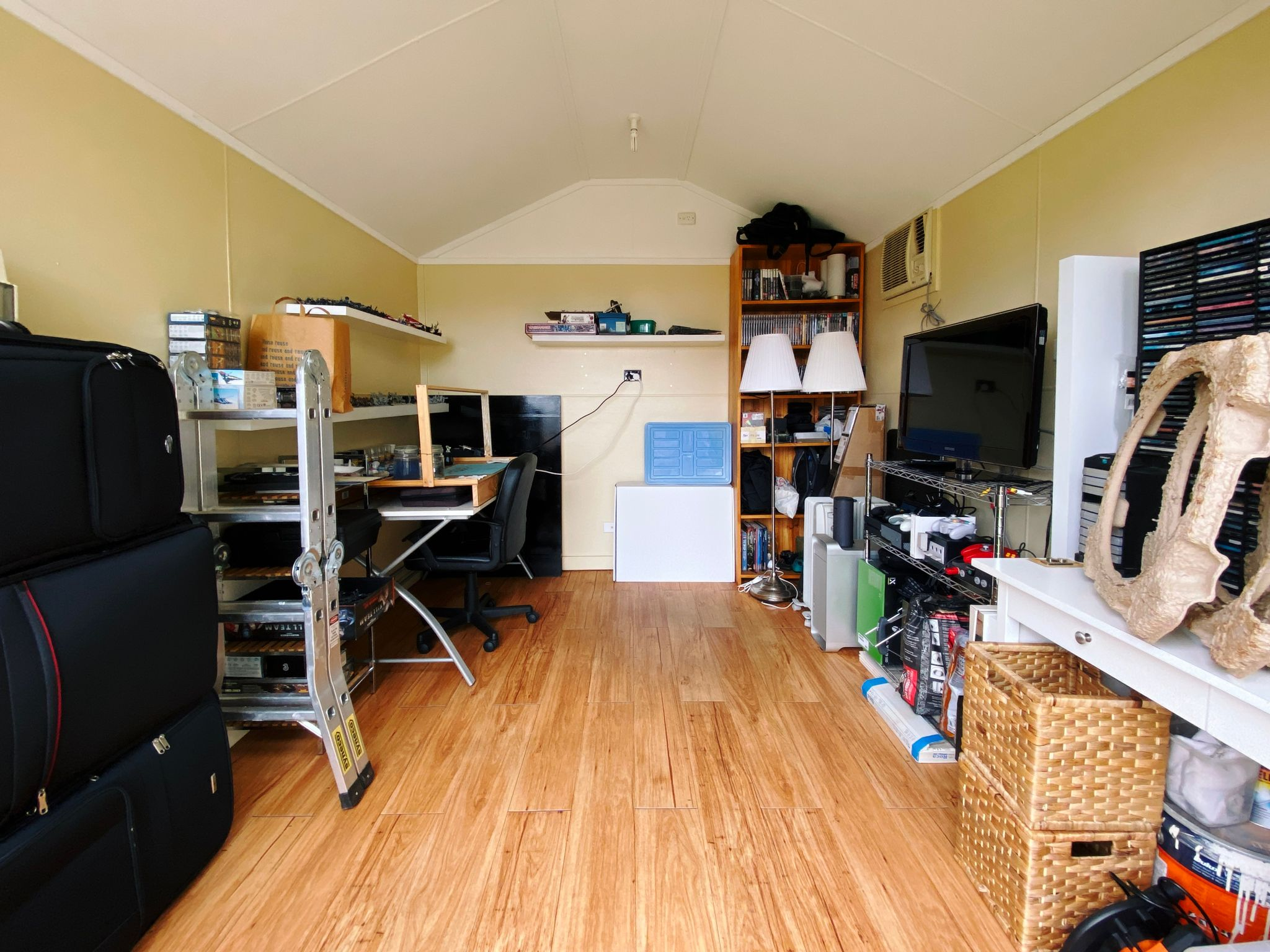 A photo of a smallish room, with stuff against all of the walls but in a neat and tidy and actually arranged fashion.