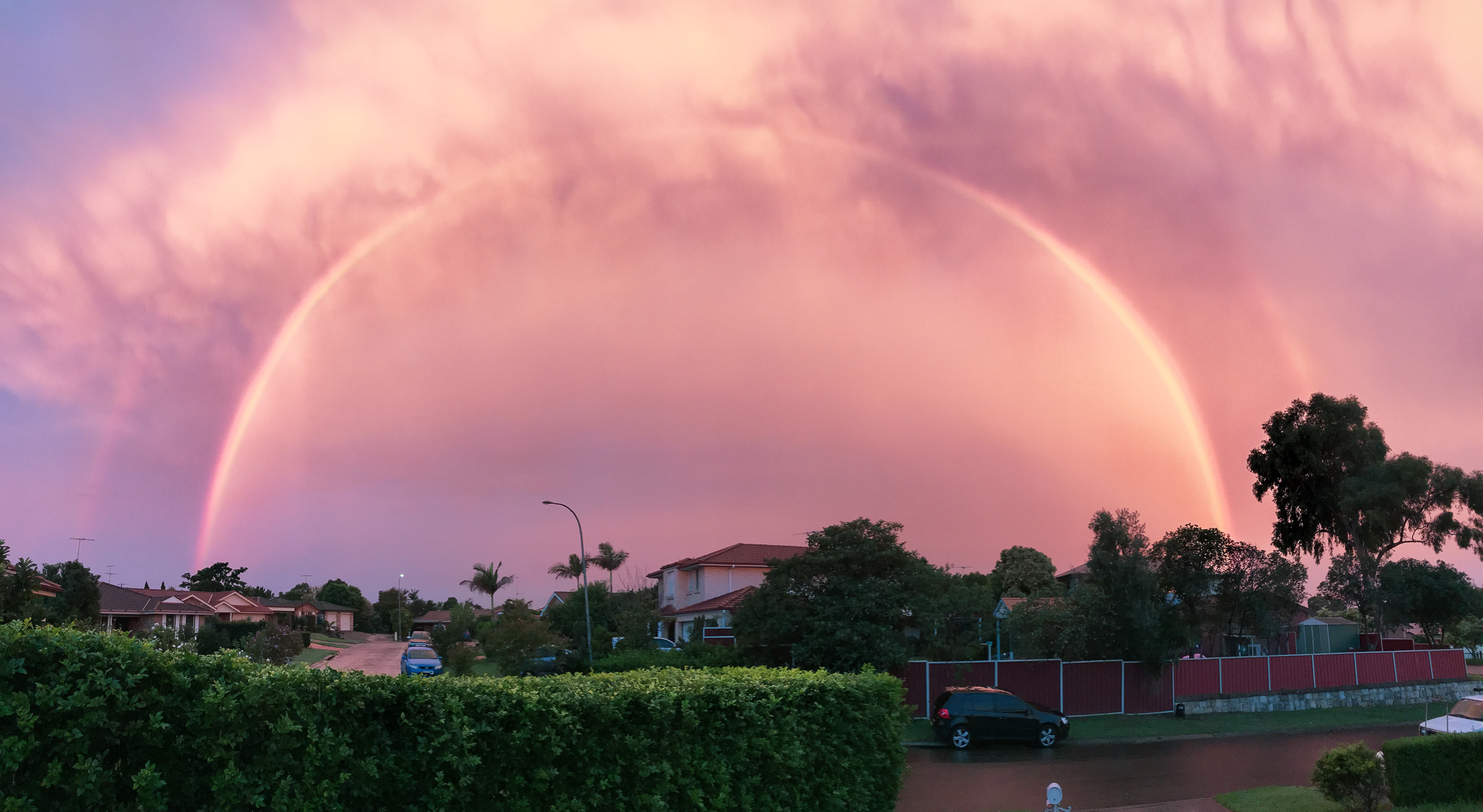 A panorama photo of a double rainbow over a suburban neighbourhood, with pink and purple clouds.