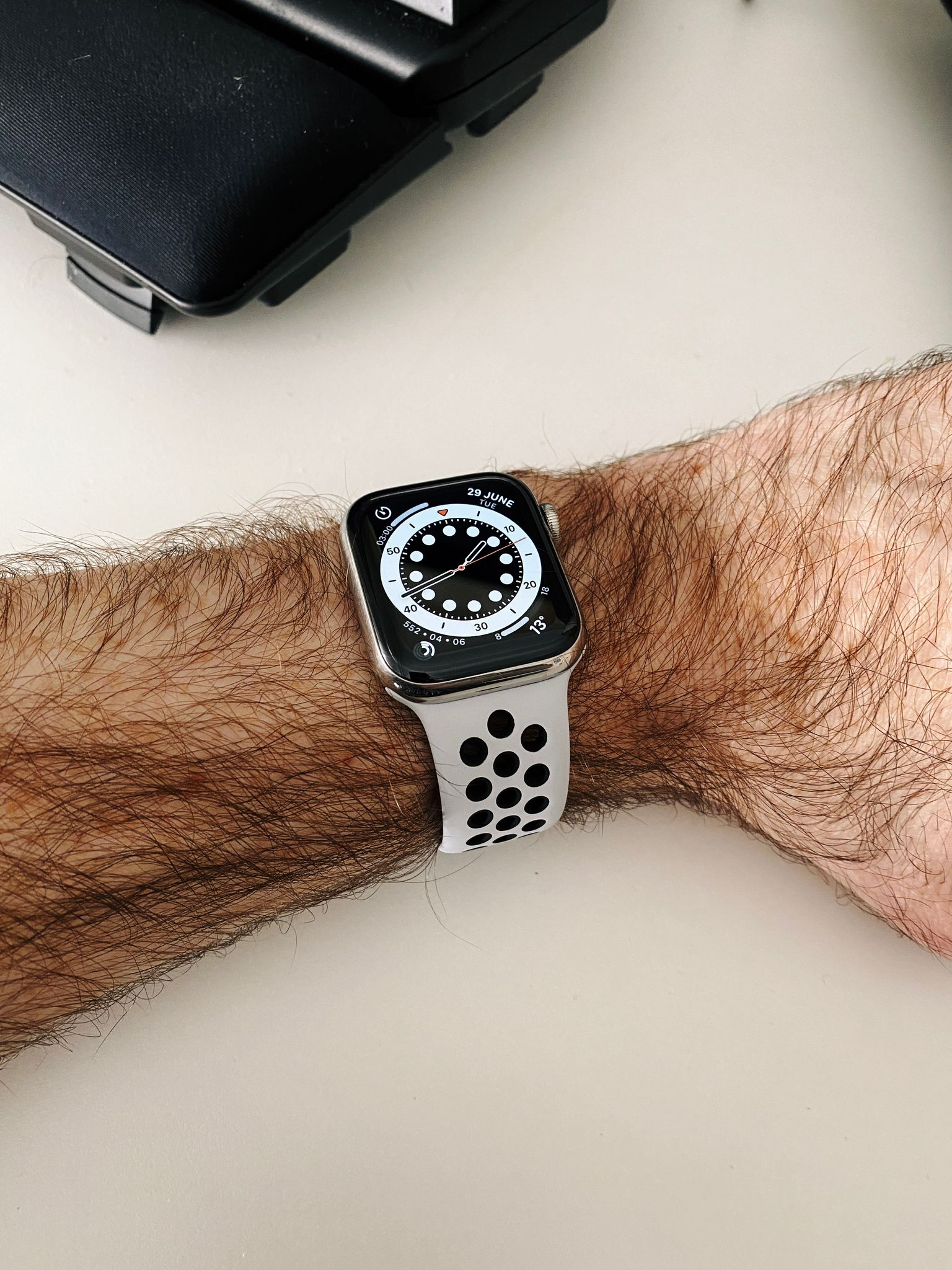 """A photo of a stainless steel Apple Watch on my extremely hairy white-man arm. The band is the Nike """"Pure Platinum"""" Sport Band, it's white with round holes along the band for breathability, and the circumference of the holes are black. It's very striking."""