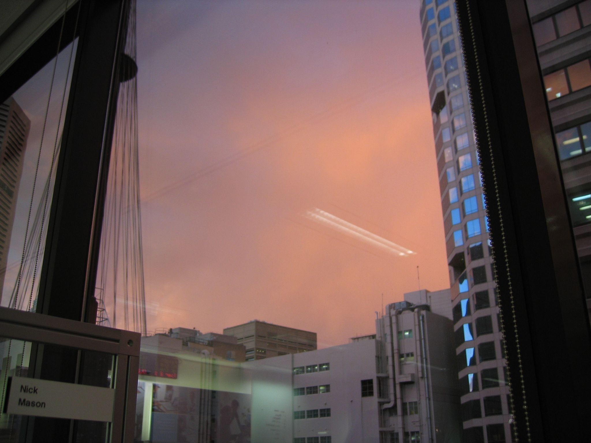 Another photo looking out the window of my work desk with duller orange clouds now fading into purple, in between a tall building on the right and Centrepoint Tower on the left.
