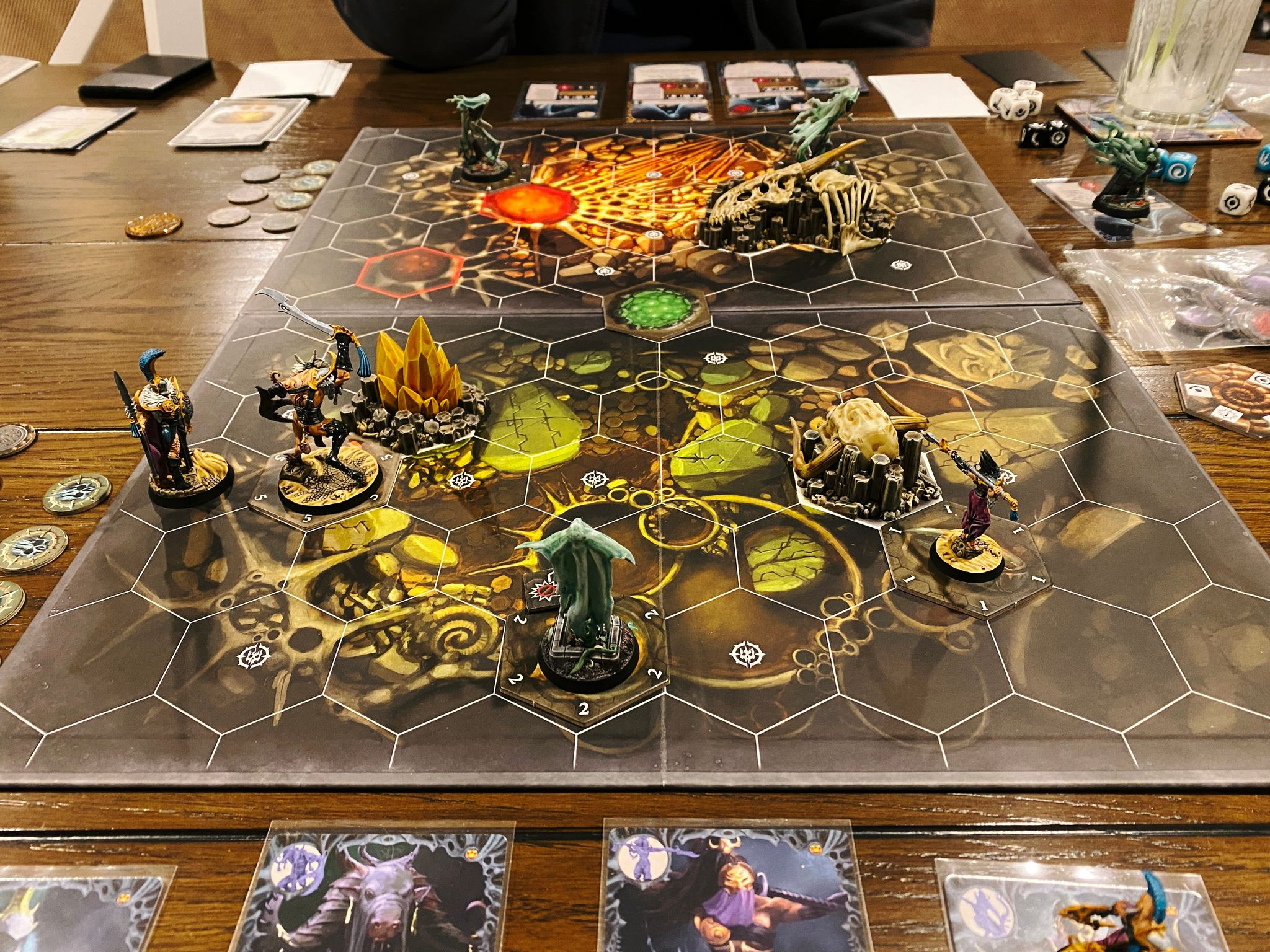 A photo of a Warhammer Underworlds game board with miniatures on it. There's also three of my new pieces of terrain: the big skeleton, the giant horned skull, and the crystals.