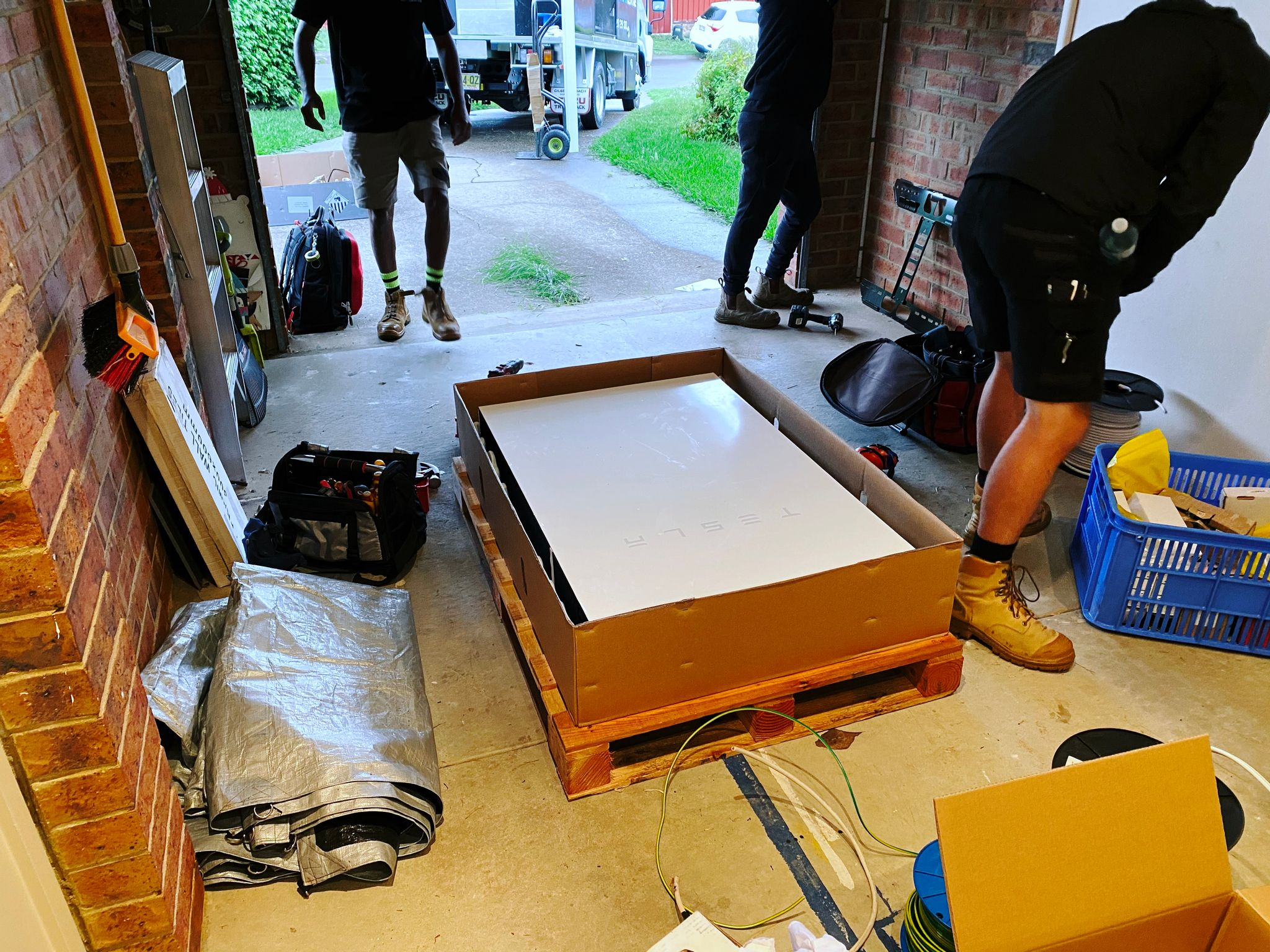 A photo of a Tesla Powerwall 2 battery sitting in its packaging on the floor of our garage, surrounded by tradies and their equipment.
