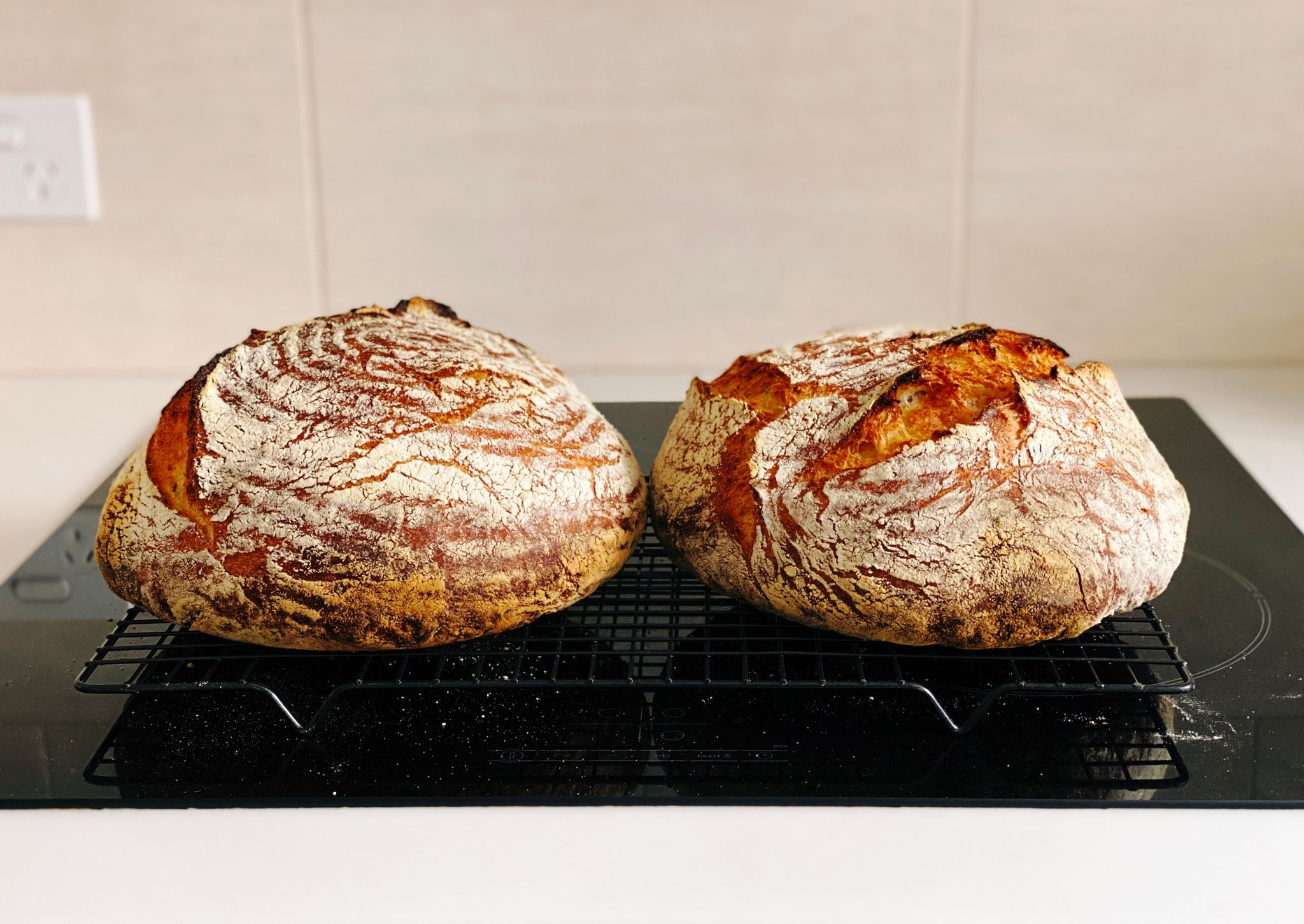 A photo of two round golden brown loaves of bread sitting on a cooling rack.