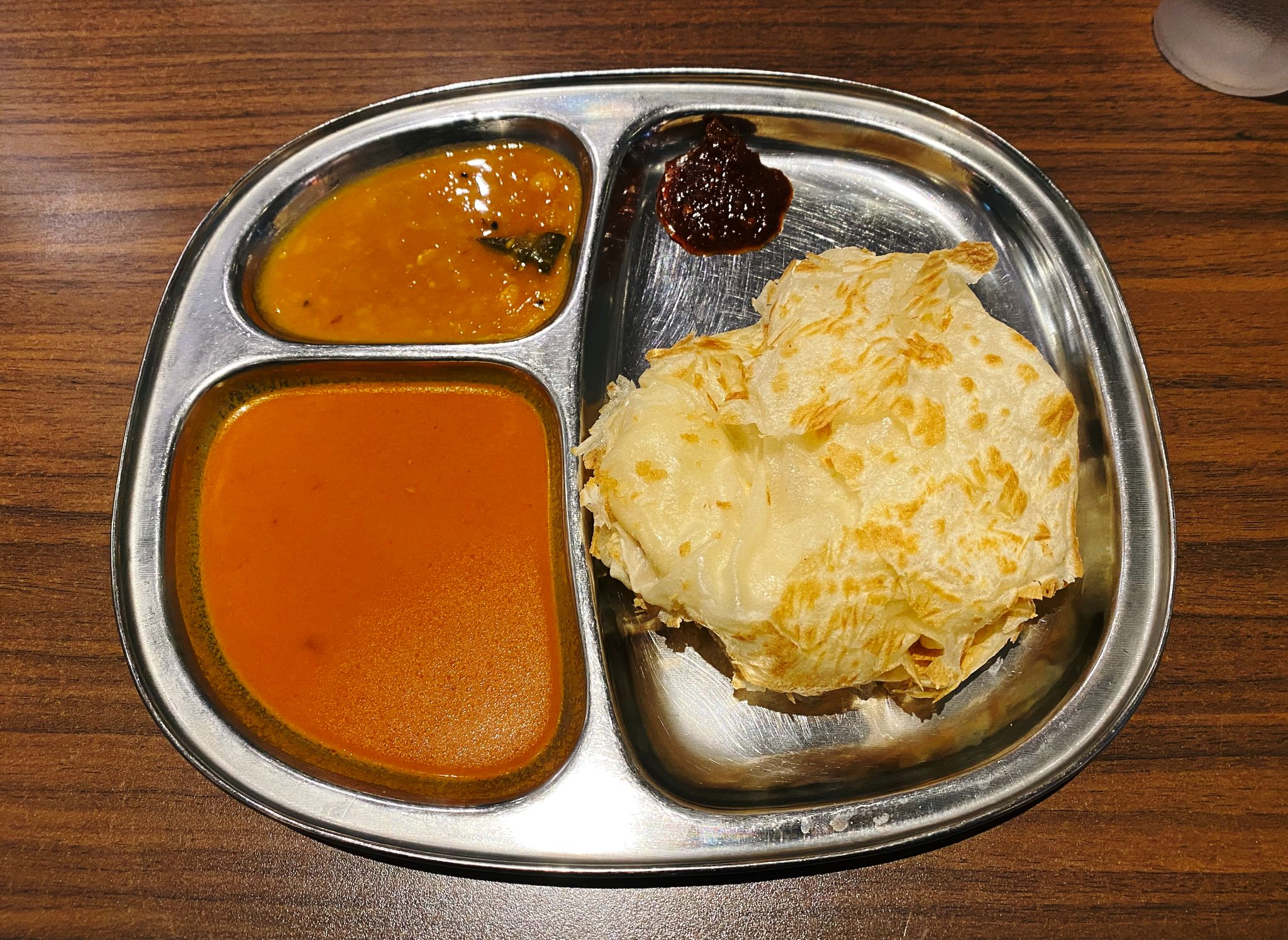 A photo of a roti canai on a plate with two different curry-type sauces for dipping.