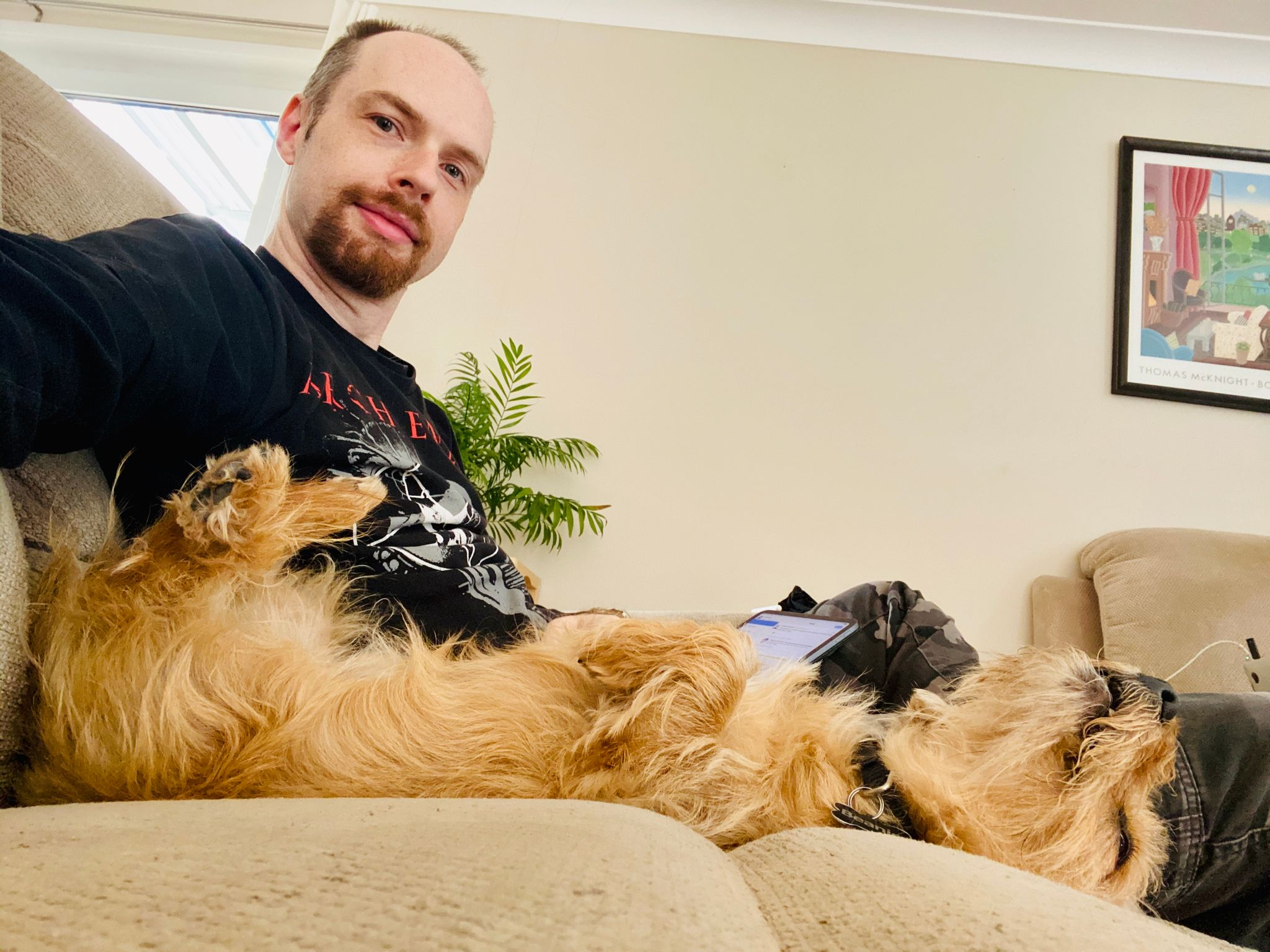 A photo taken from the side showing me, a white male with brown hair and a red goatee, and the blonde scruffy dog clearly with his back legs in the air as he's lying upside-down.