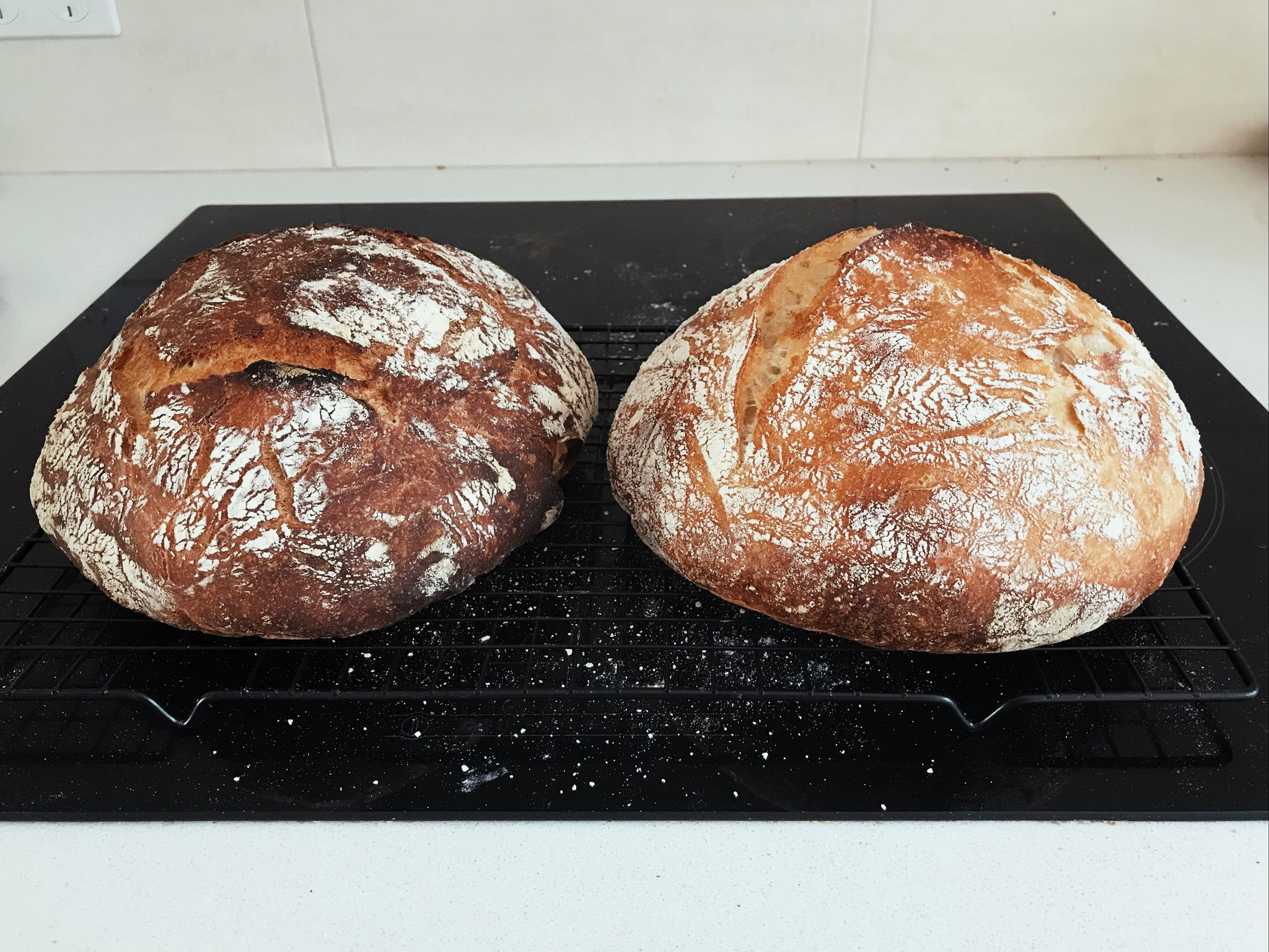 Two round loaves of bread on a cooling rack, the left one being noticeably browner than the right one.