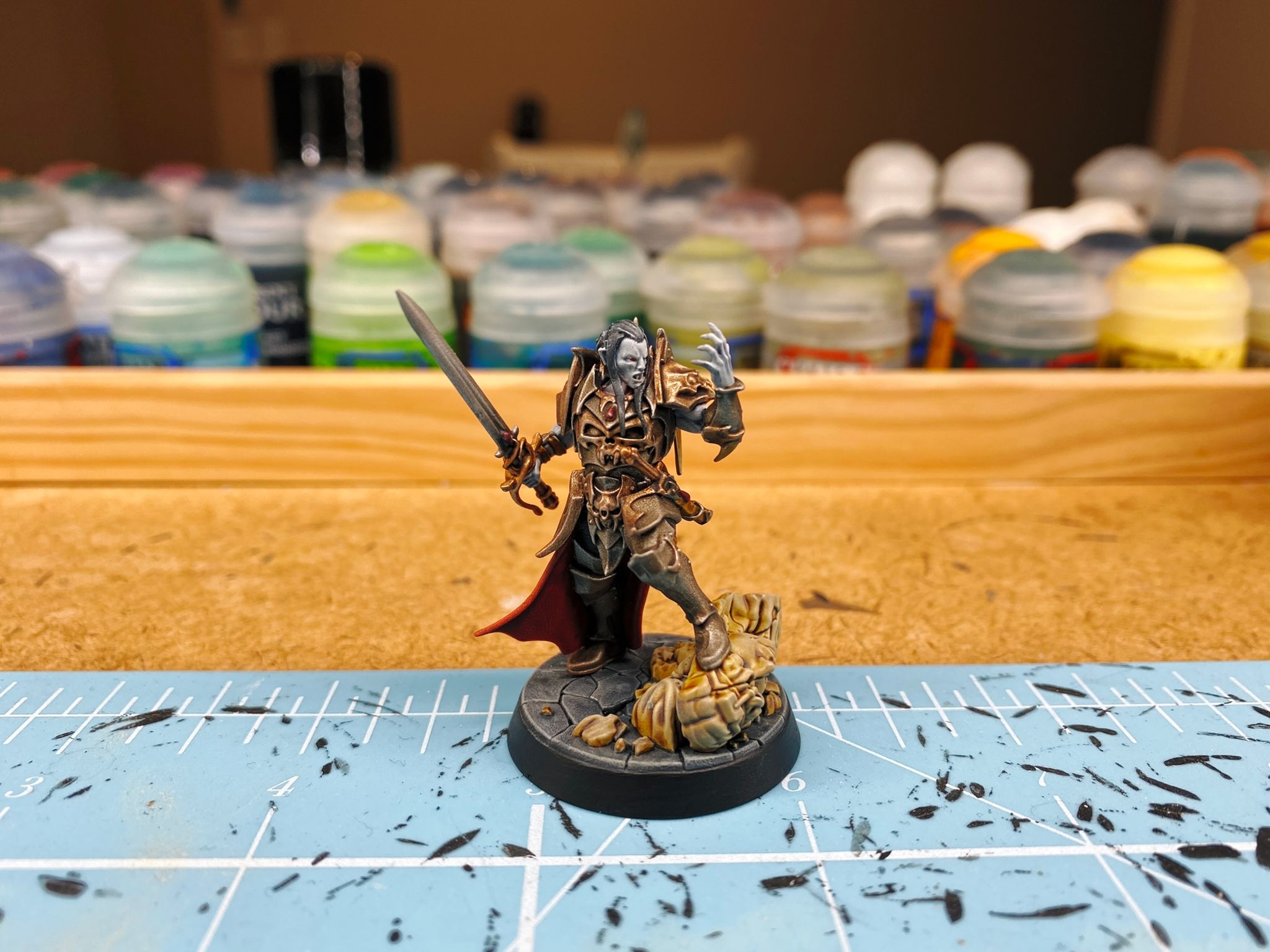 """A photo of a vampire miniature. His skin is very pale blue like he's dead (which is he, because he's a vampire), he's wearing steel- and brass-coloured armour with a blood red cloak, he has a sword in one hand, and his other hand is held up in front of him in a sort of """"We will crush them"""" pose. His front foot is resting on top of the broken-off head of a stone statue."""