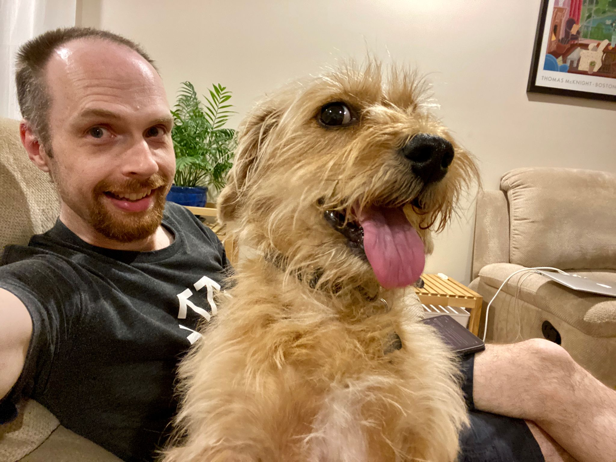 A small scruffy blonde dog right in front of the camera with his mouth open panting which makes him look like he's smiling, with me, a white man with a red goatee, in the background. We're both looking at the camera.