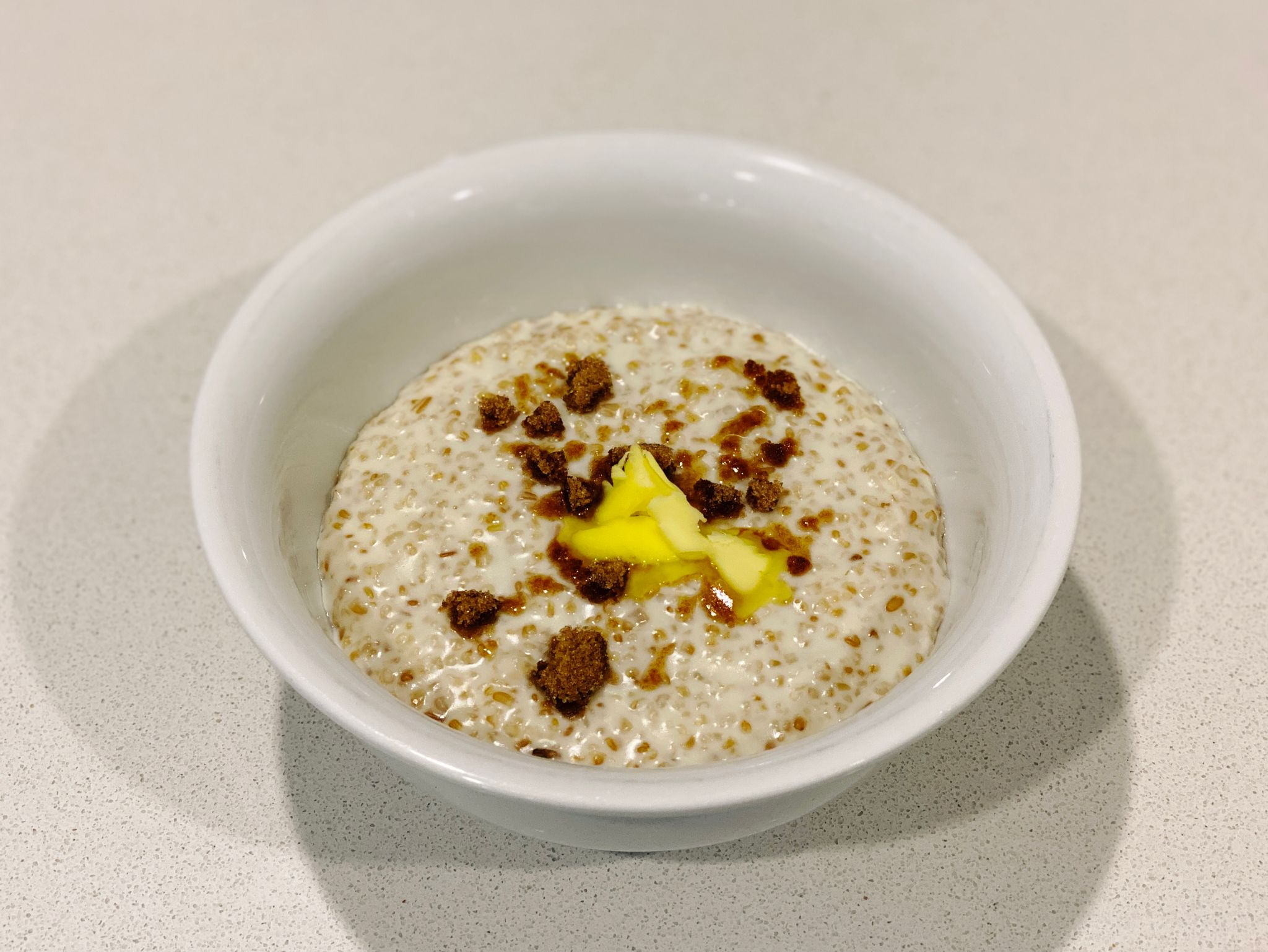 A photo of a bowl of porridge with brown sugar and a dollop of butter on top.